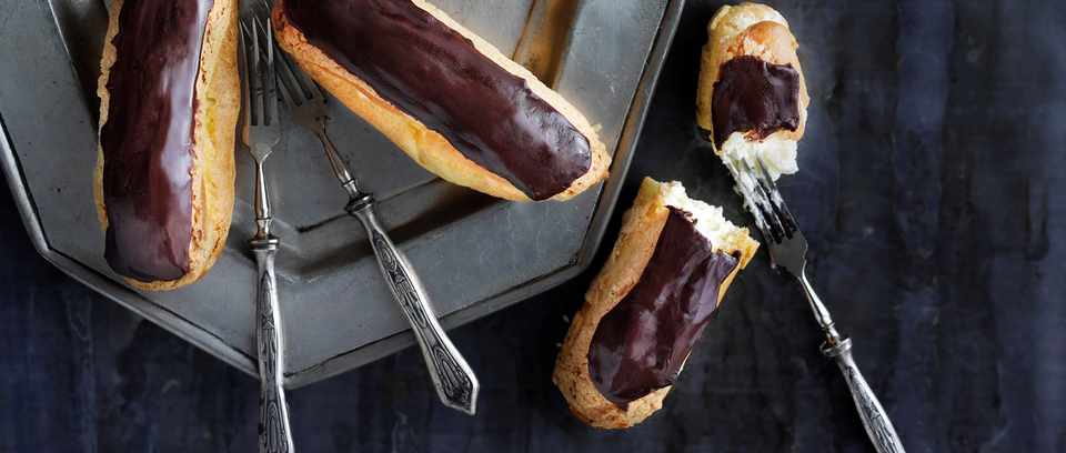 Chocolate éclairs on a dark background with forks
