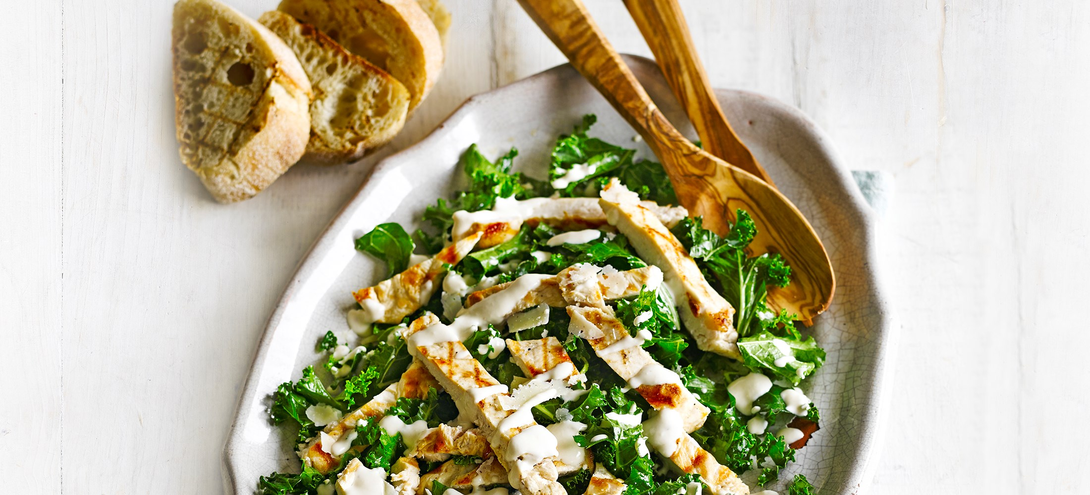 Kale Chicken Caesar Salad served on a pale white oval plate