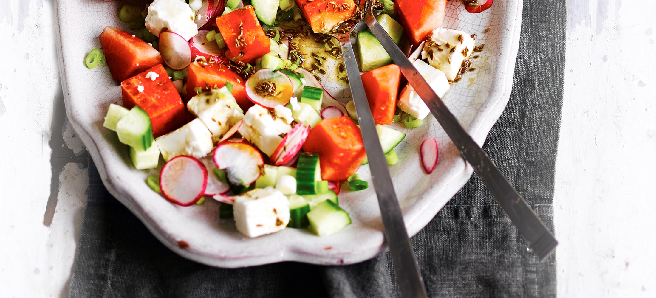 Watermelon Salad with Feta Recipe and Pomegranate dressing served on an oval light coloured serving dish with a salad spoon and fork for serving