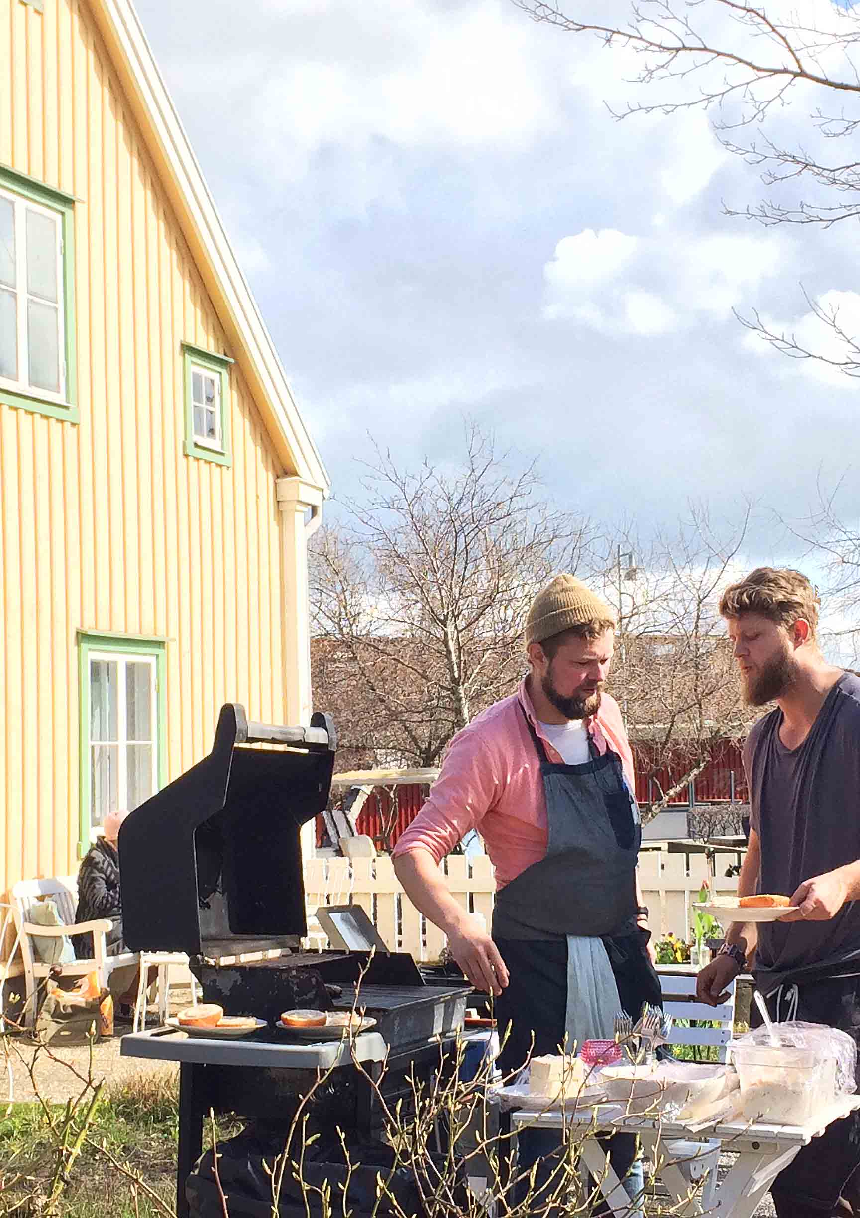 Two men outside at a BBQ with a yellow house in the background