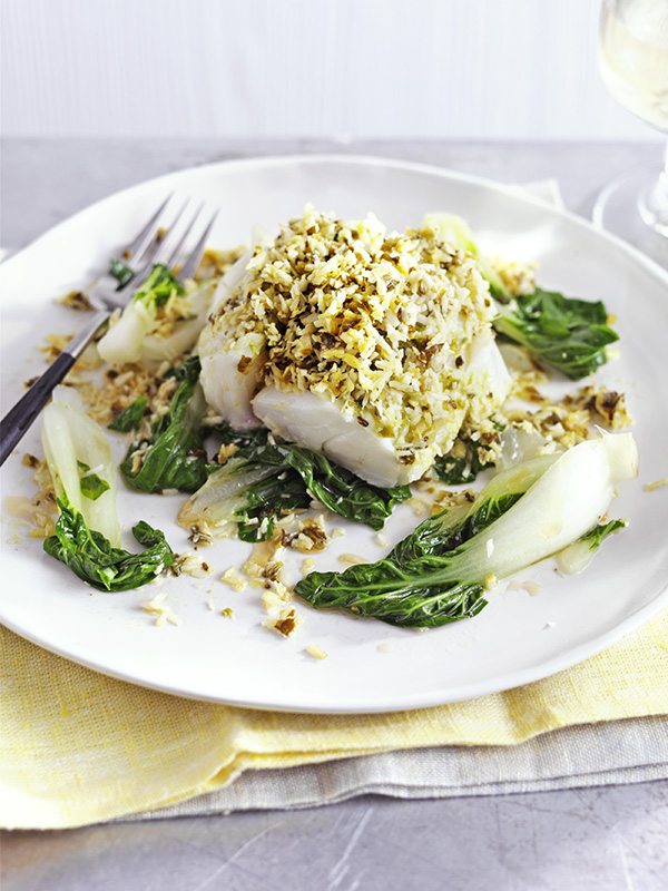Fish Parcels Recipe with Coconut and Ginger served with bak choi on a white plate