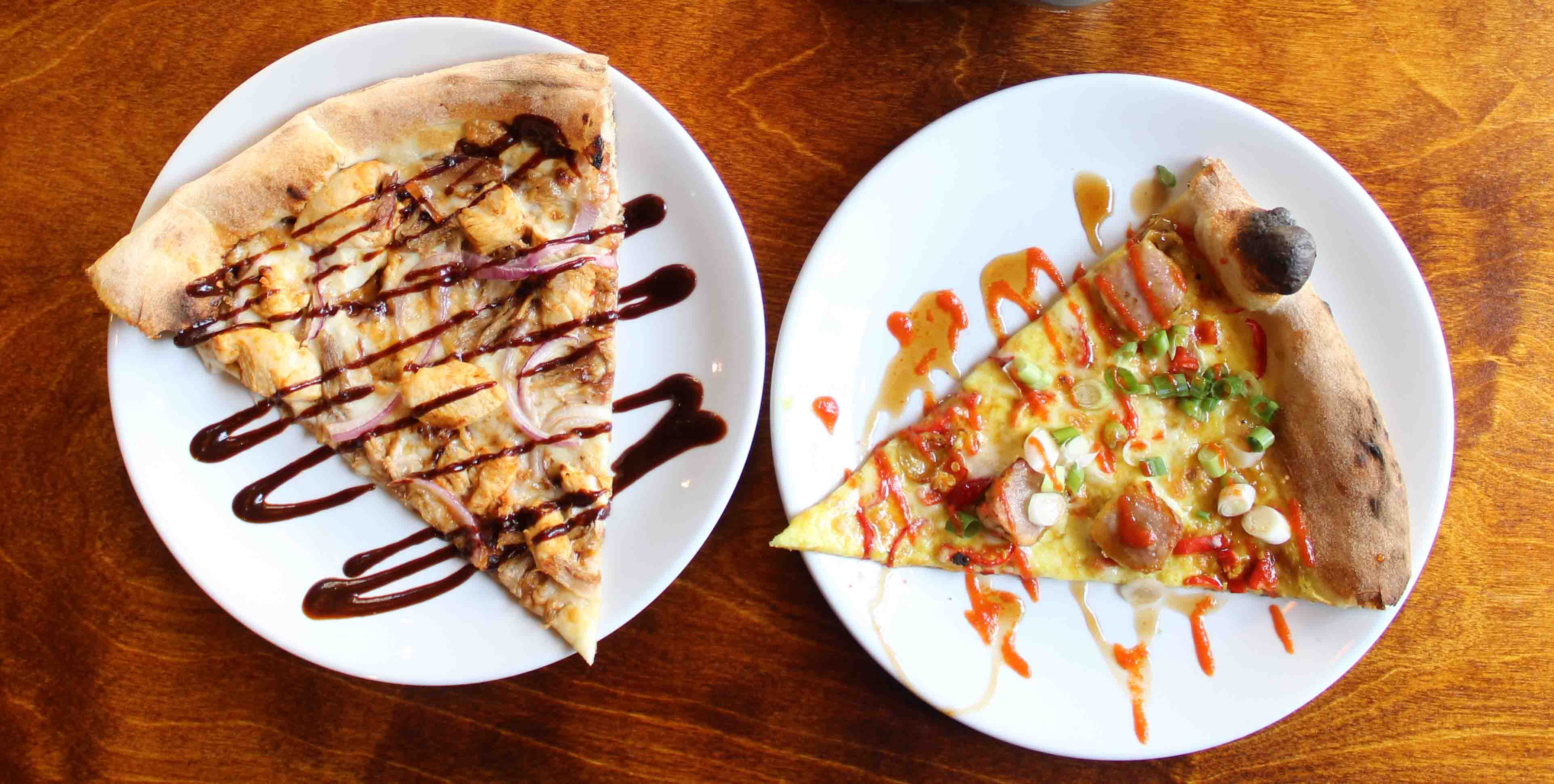 Two white plates each topped with a slice of pizza and drizzled with sauce at Santa Maluco, Liverpool