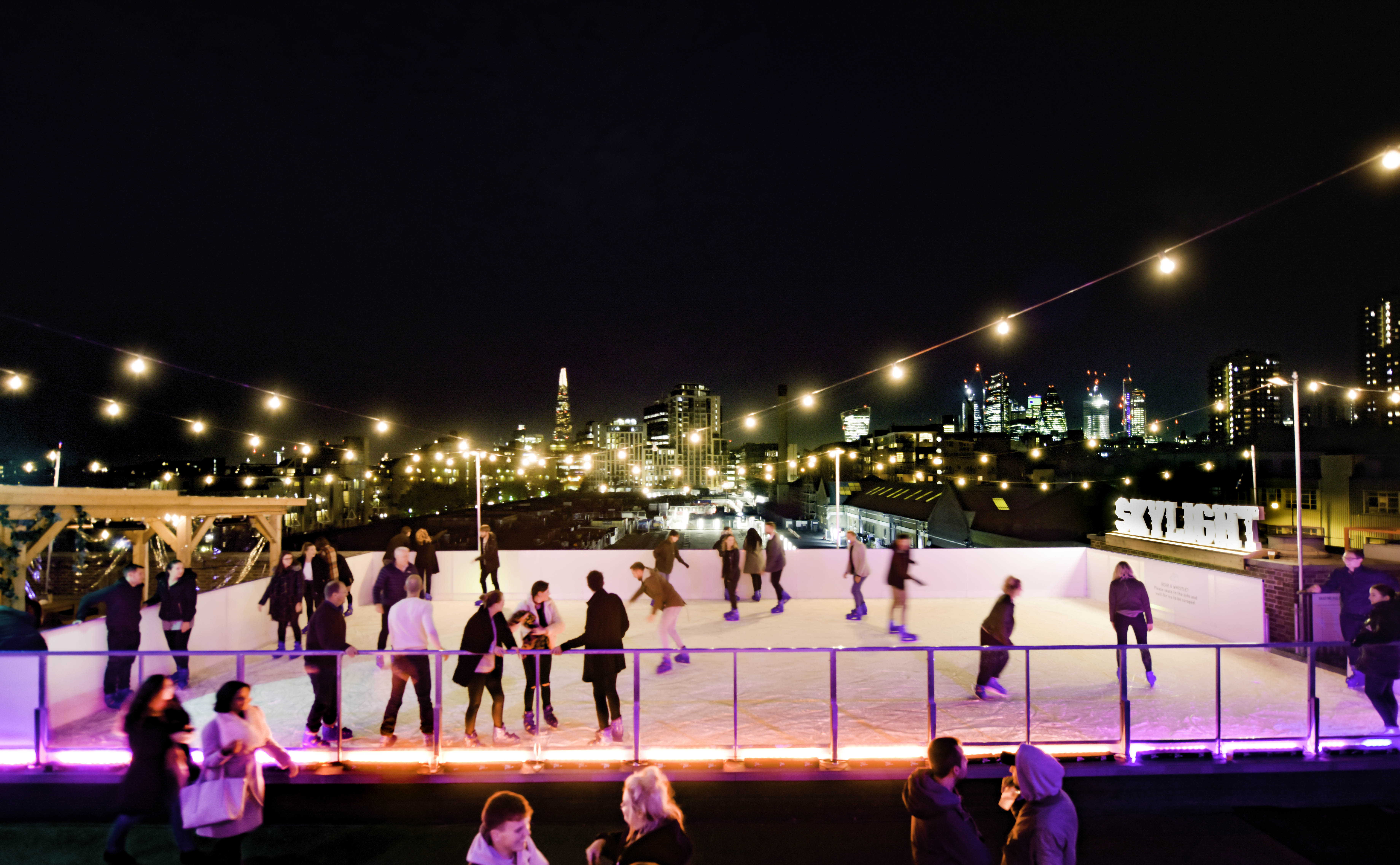 The rooftop ice skating rink at Skylight, Tobacco Dock. There is the London skyline in the background and people are skating around on the ice