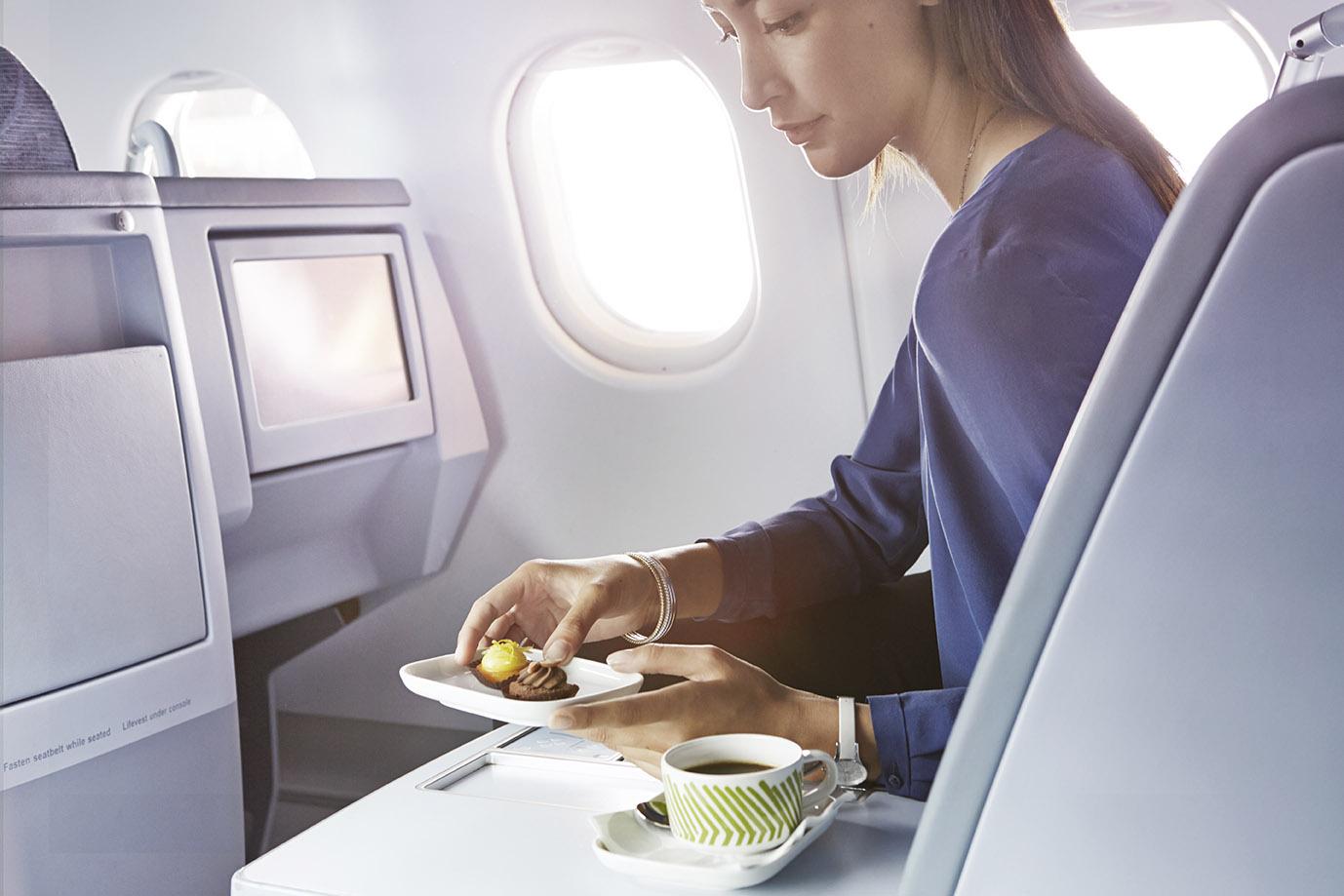 finnair-business-woman-having-a-dessert on a plane