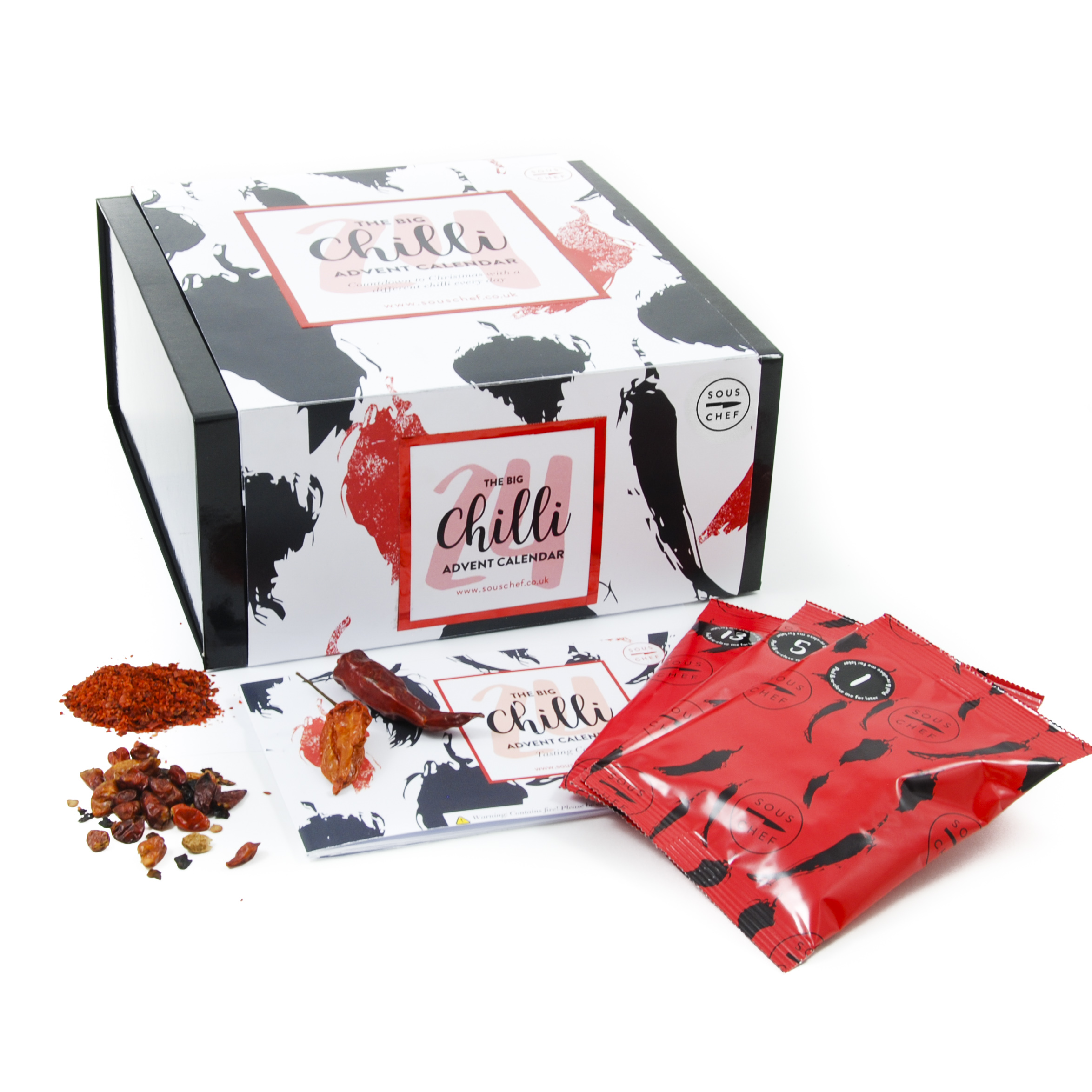 Chilli advent calendar sous chef. The box is black with a white sleeve which has images of chillis drawn in black and red. Outside of the box there are a few chillis outside the box and sachets of chilli too