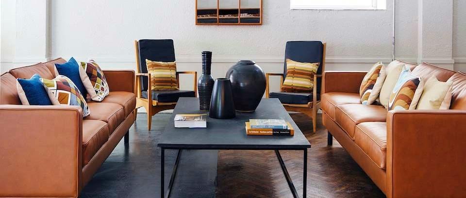 orange leather sofas around black trendy coffee table