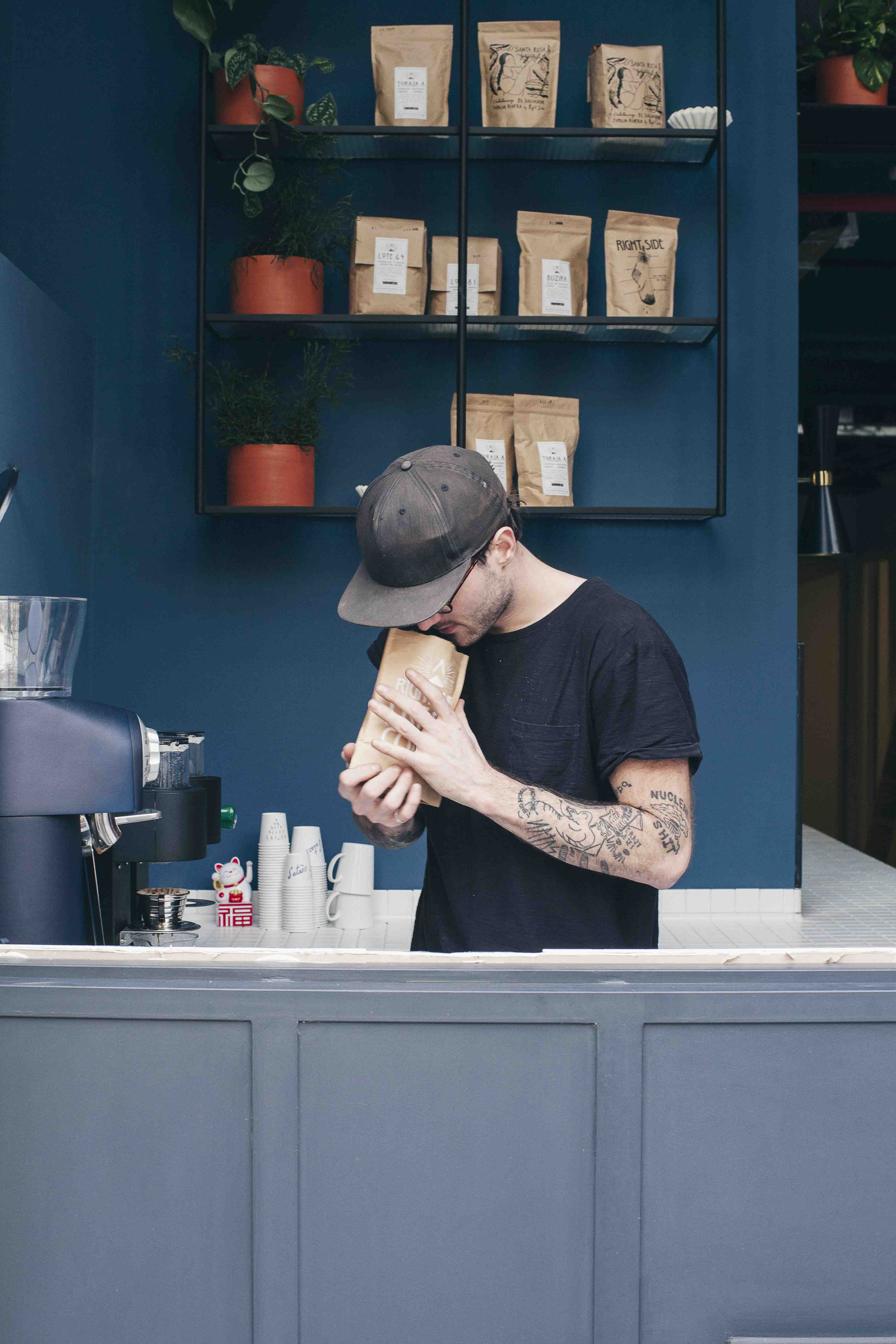 Man in cap smelling coffee from a brown bag behind a dark blue shop counter