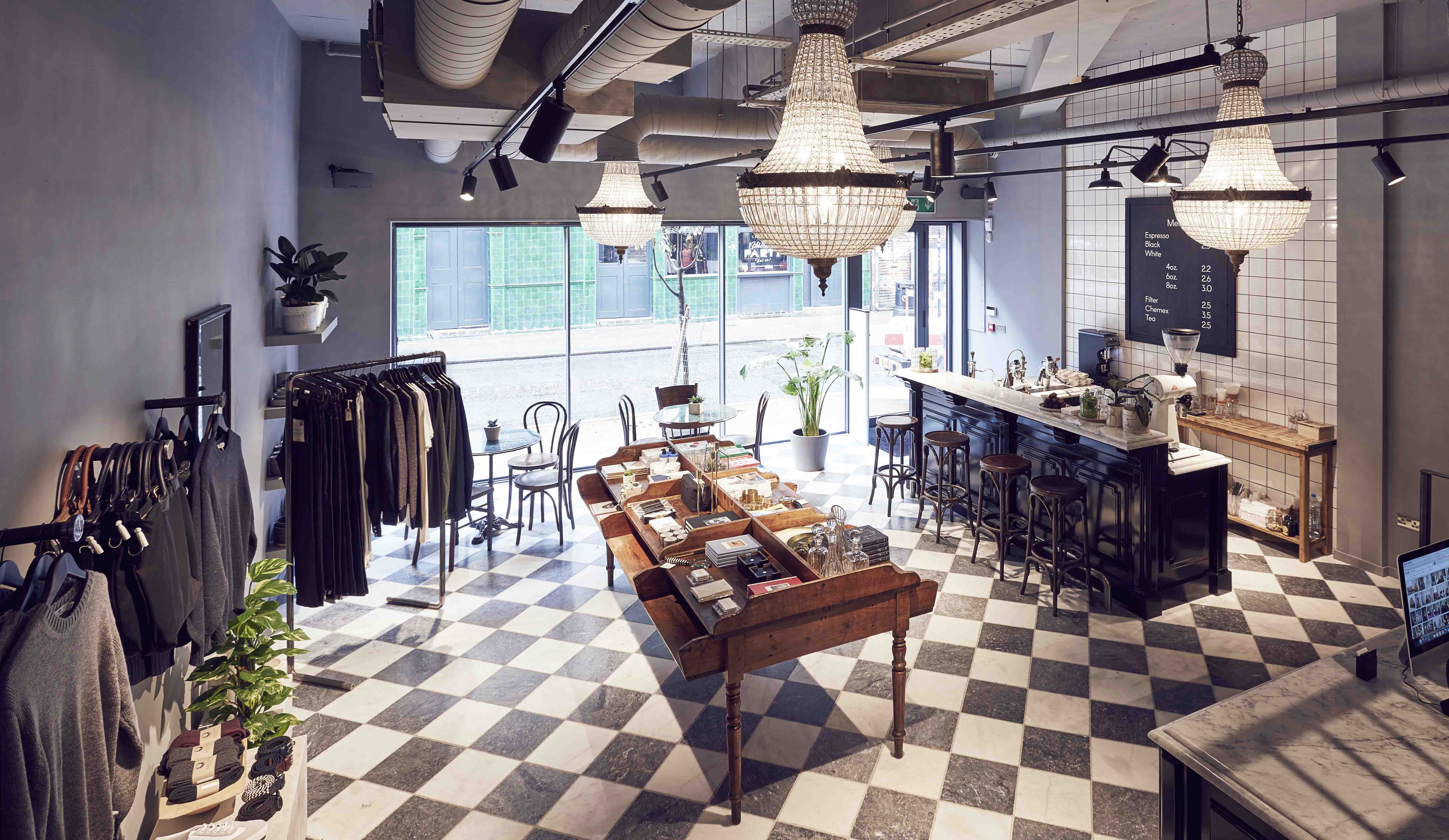 Shop overview with black and white tiled floor, a bar to the right and clothes rails to the left