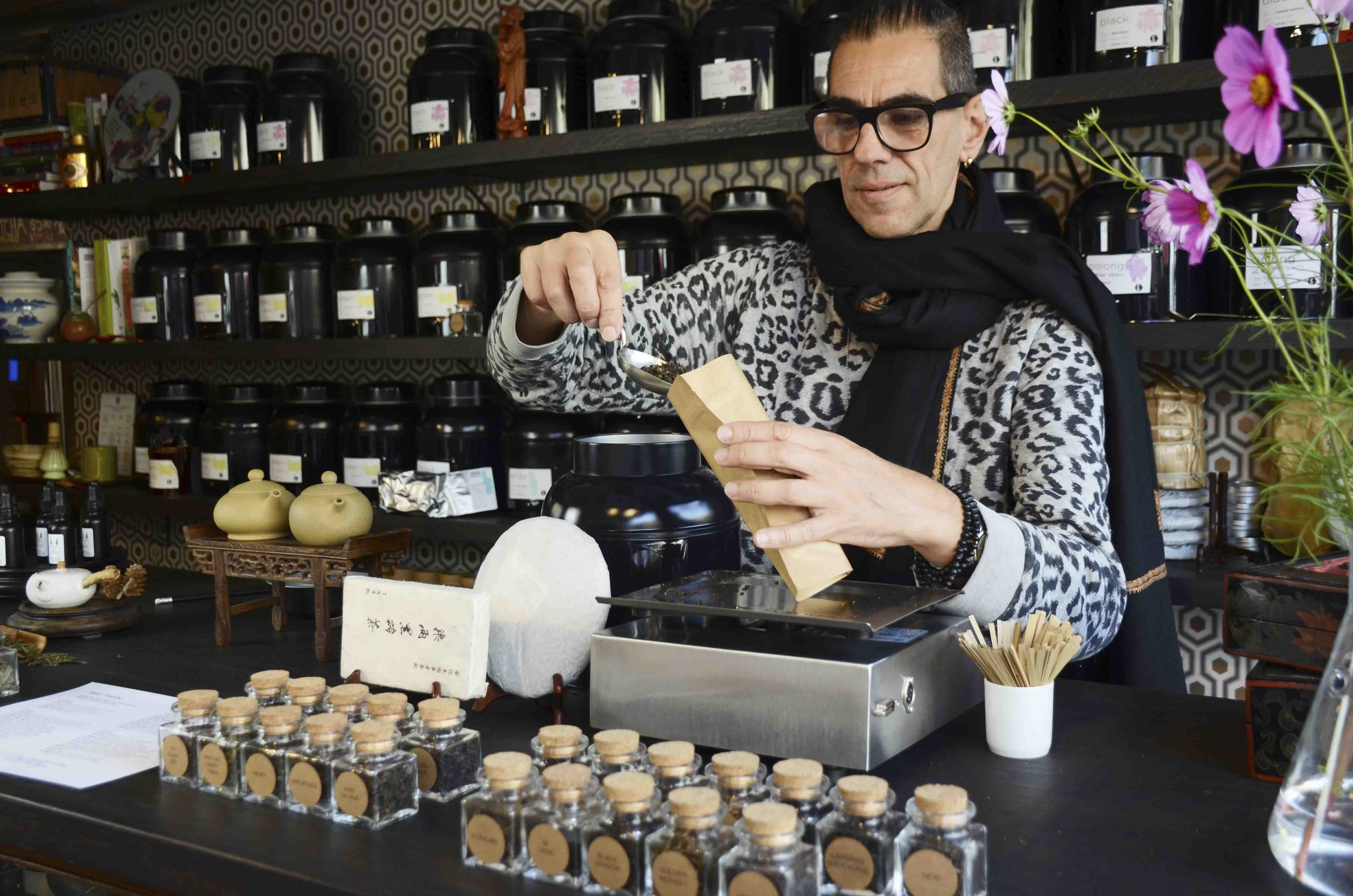Man in jazzy shirt and black scarf weighing out tea in a shop