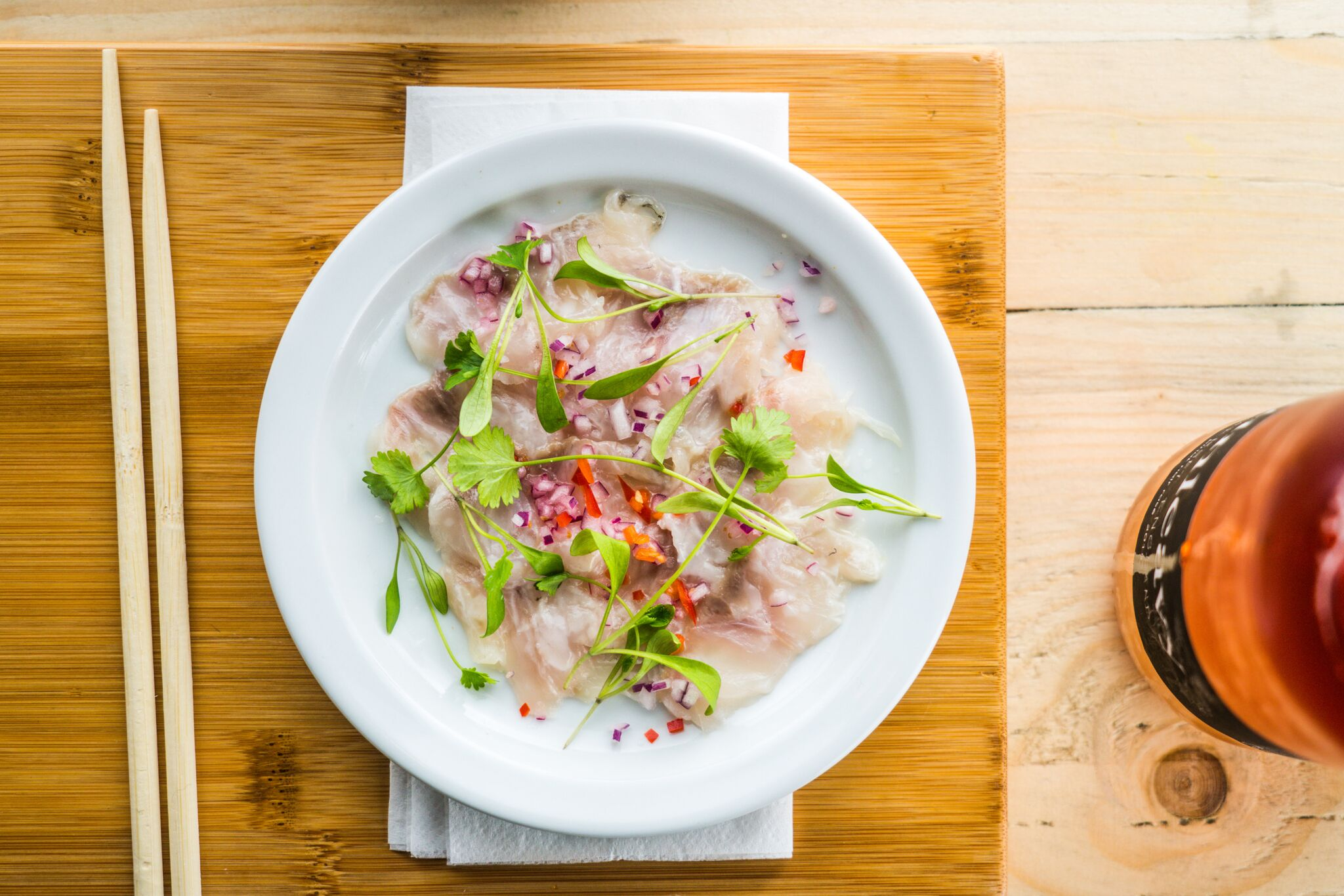 Seabass Tartare (sushi grade), caramelised daikon, lime and chilli served with chopsticks
