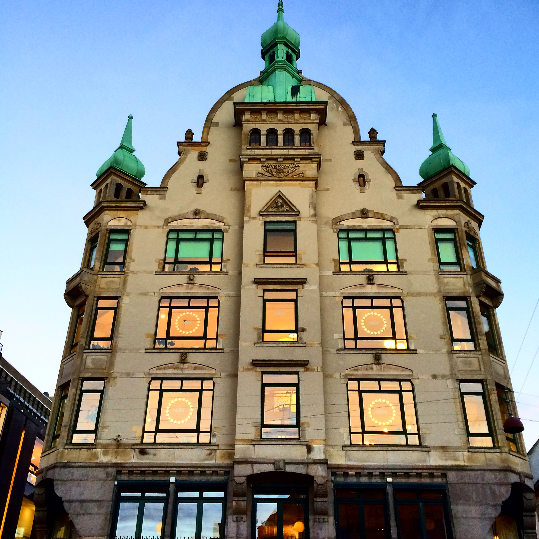 HAY House Copenhagen with orange glow from windows, turqouise turrets