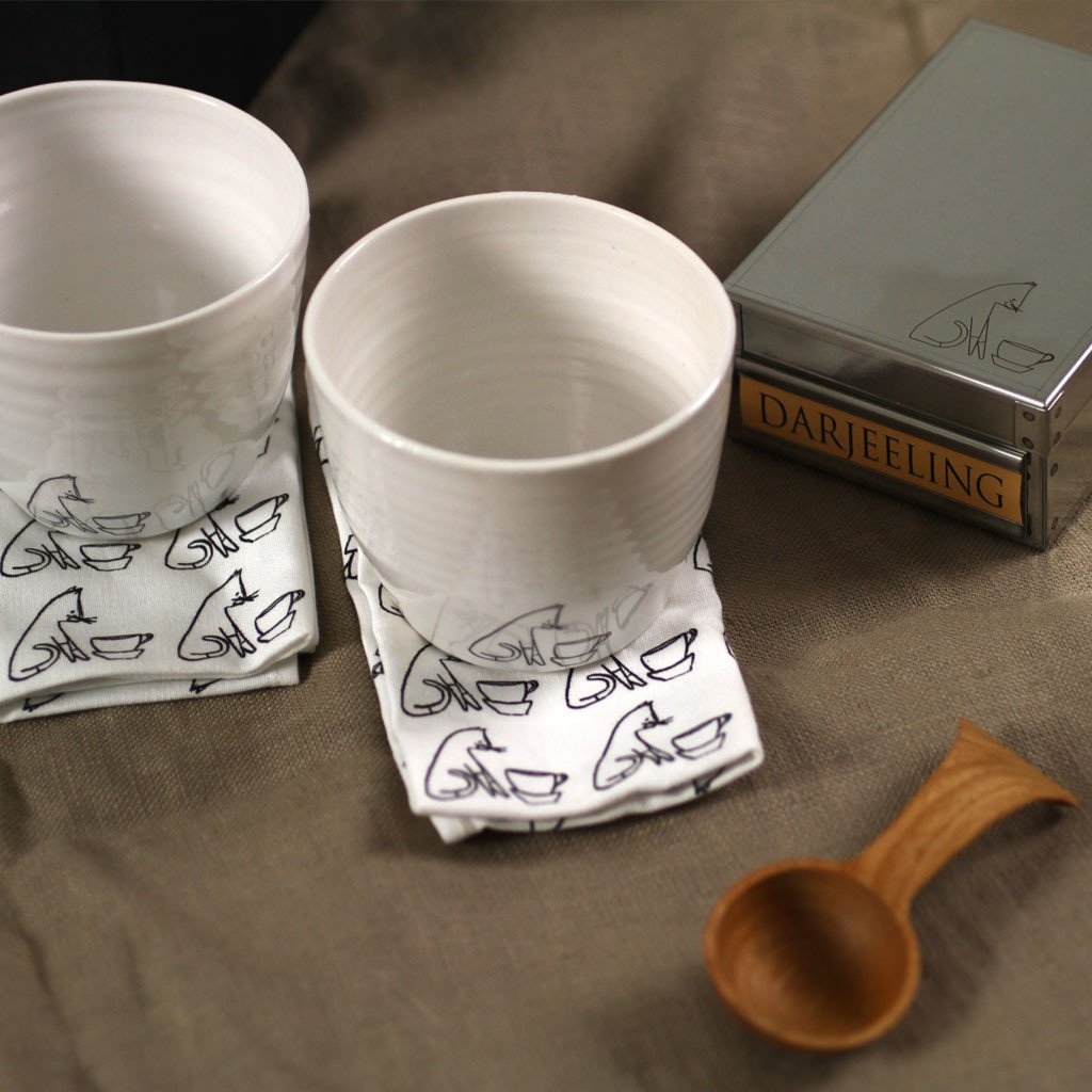 Two tea cups with a tea caddy and a wooden scoop