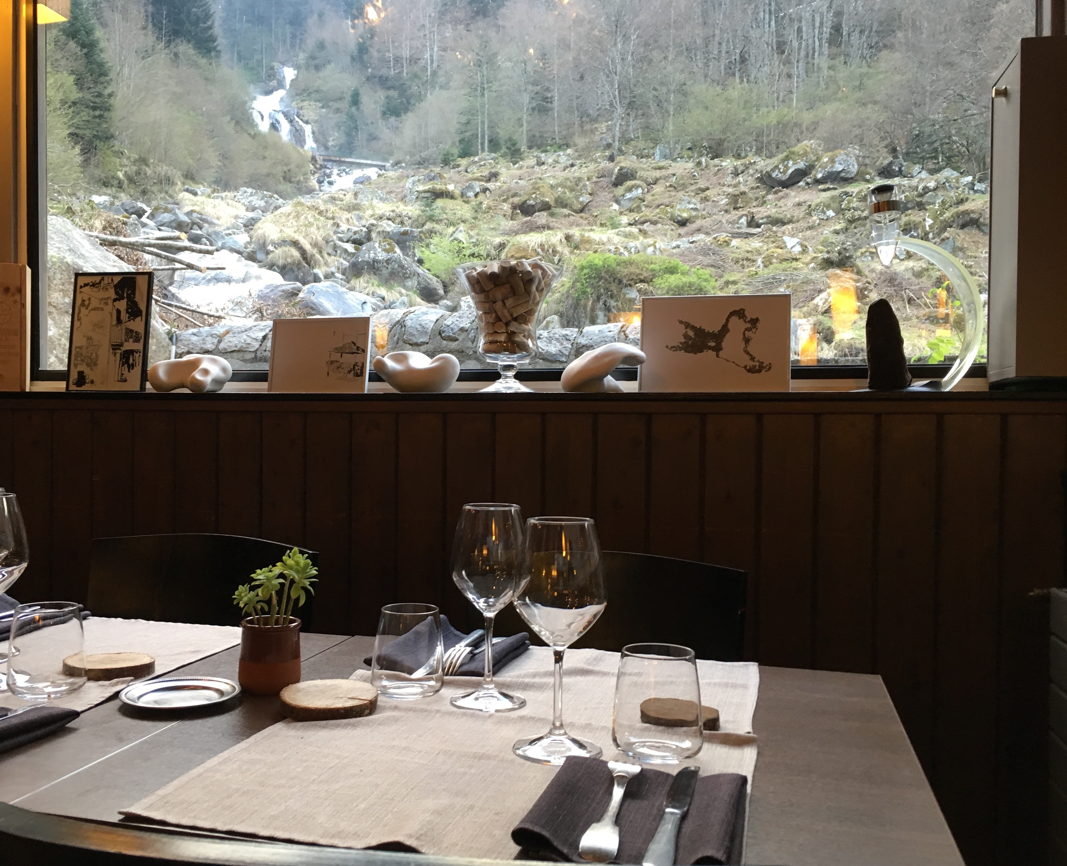 Table set with glasses and cutlery with a view out over the stream at L'abri du benques