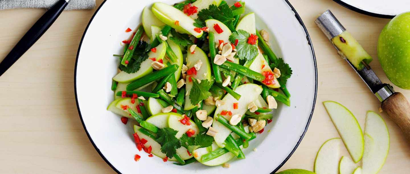 Bowl of salad with apples, green beans and peeler at the side