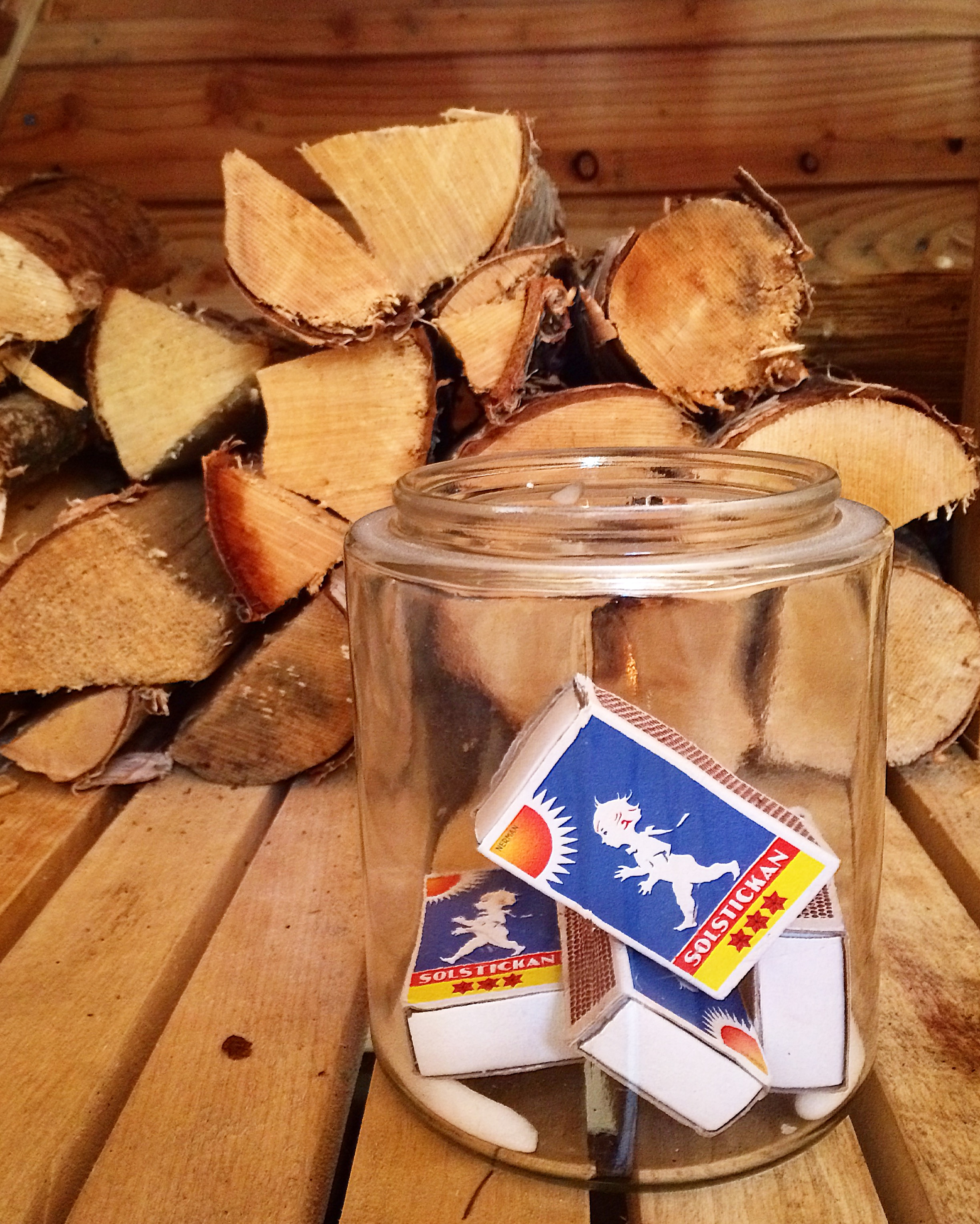 Swedish Solstickan matches in front of chopped wood in a sauna