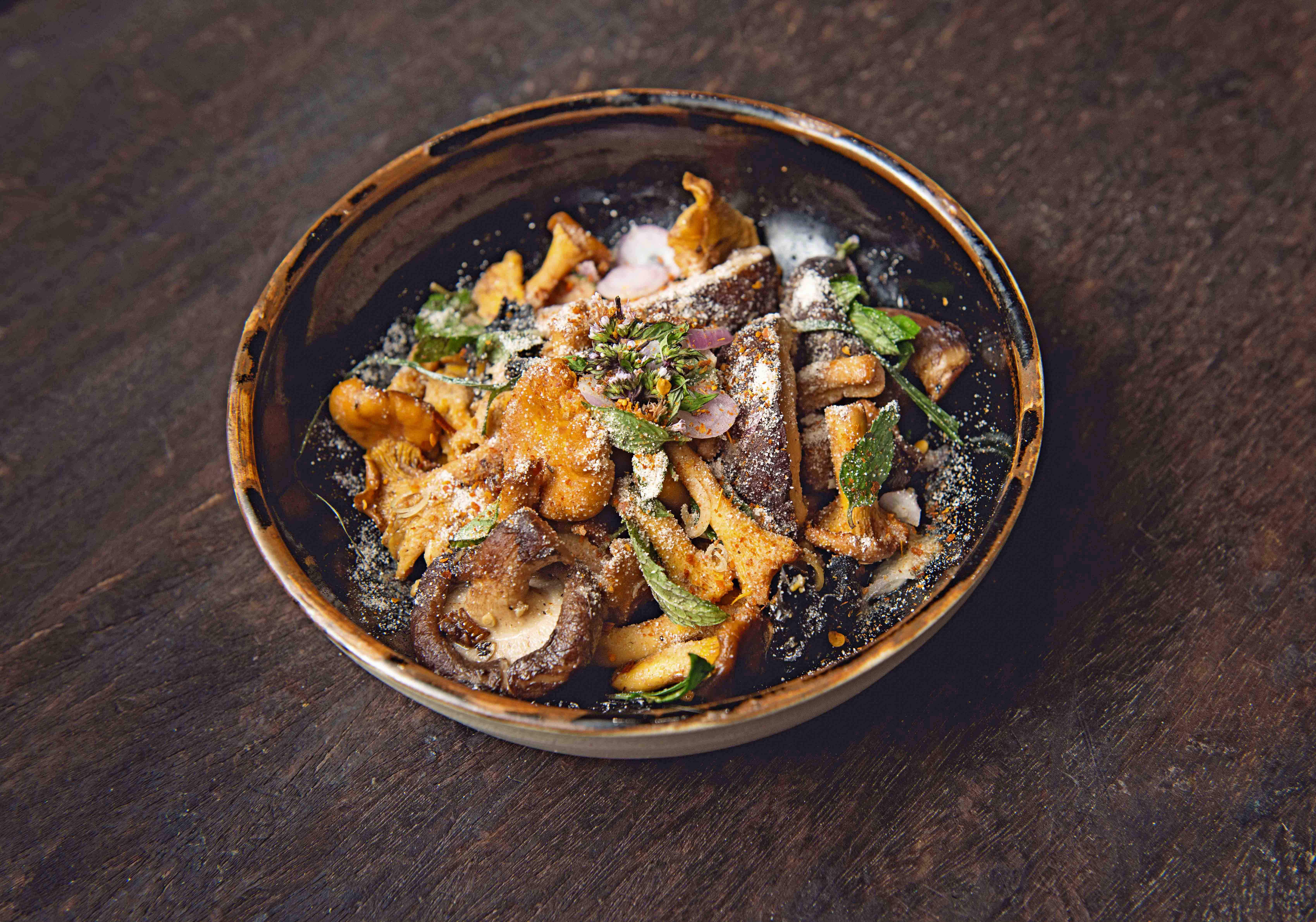 Small bowl of wild mushrooms with green leaves on top