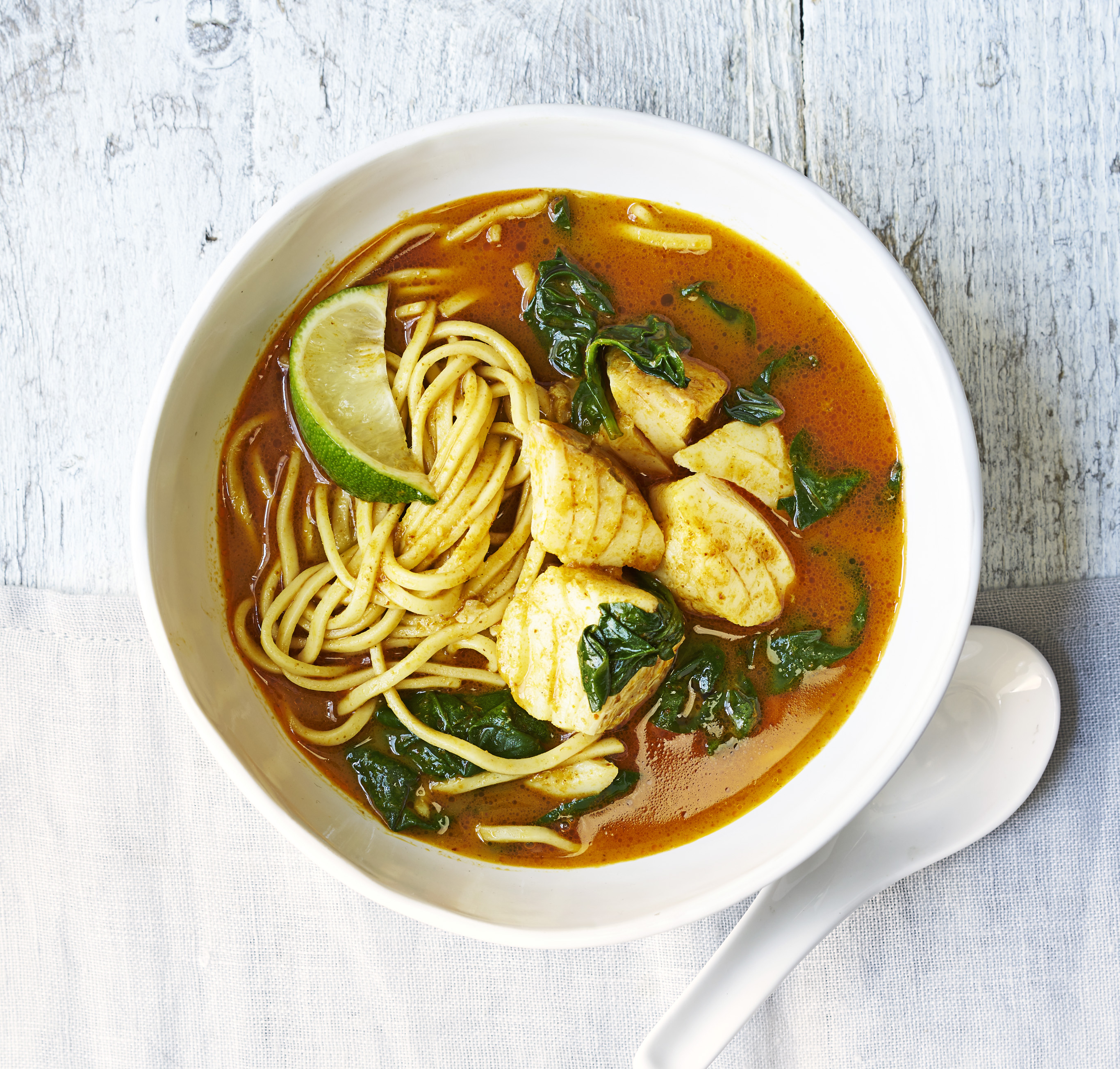 A warming bowl of Thai style coconut fish egg noodles with cod, spinach and limes