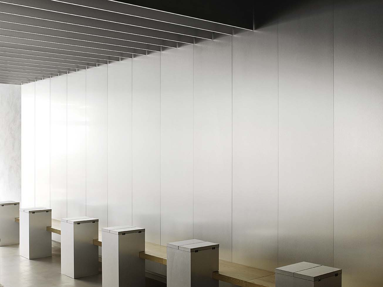 A room with an aluminium wall, wooden bench and small folding wooden tables