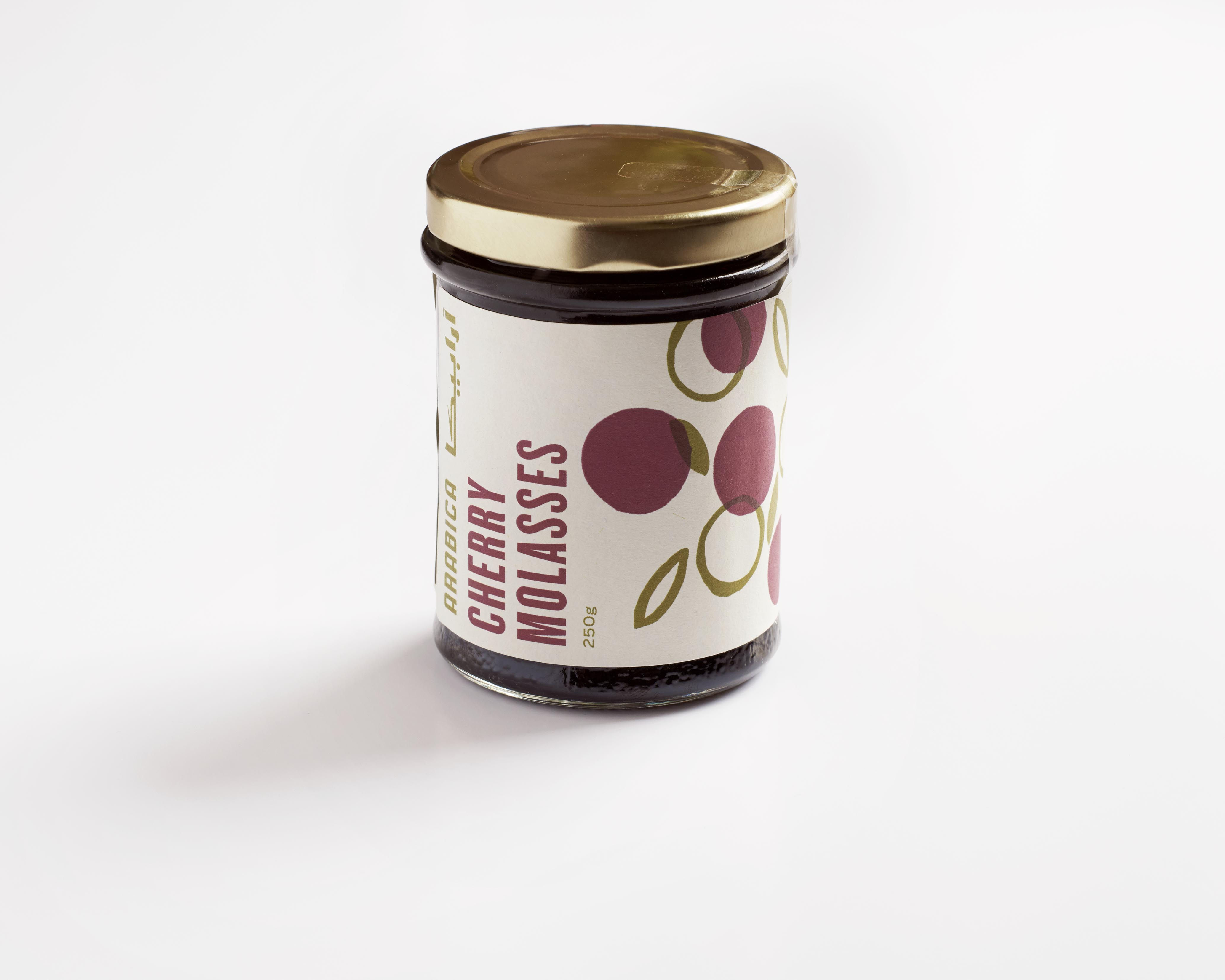 A jar on a white background. The jar is filled with Arabica Food & Spices Cherry Molasses. There is a label on the front with drawing of cherries and a gold lid on top