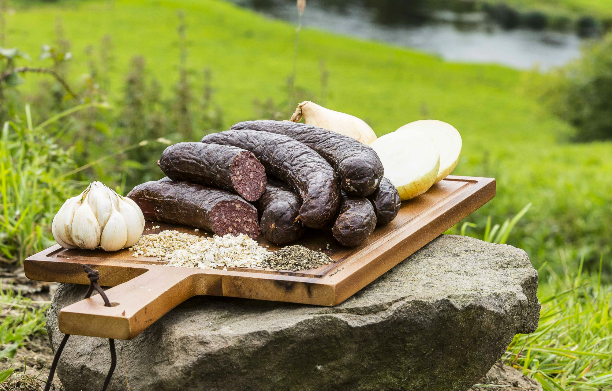 A wooden tray topped with six Smoked Black Pudding. There is grass in the background