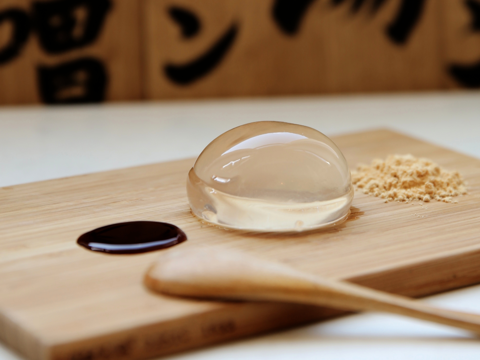 Raindrop cake on a wooden board with a wooden spoon