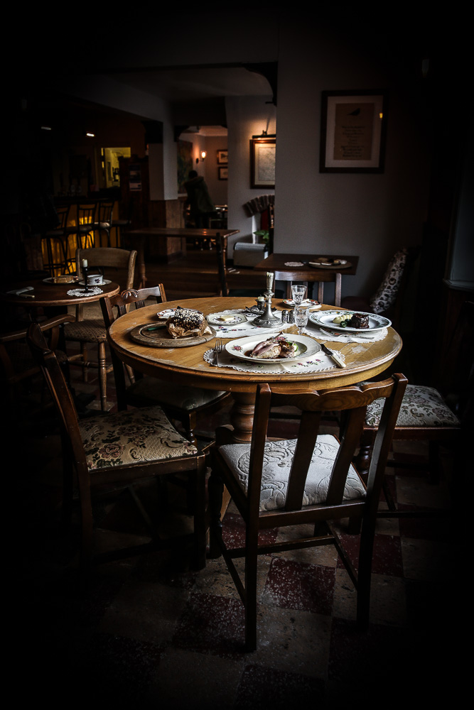 A wooden table laden with food inside a country pub