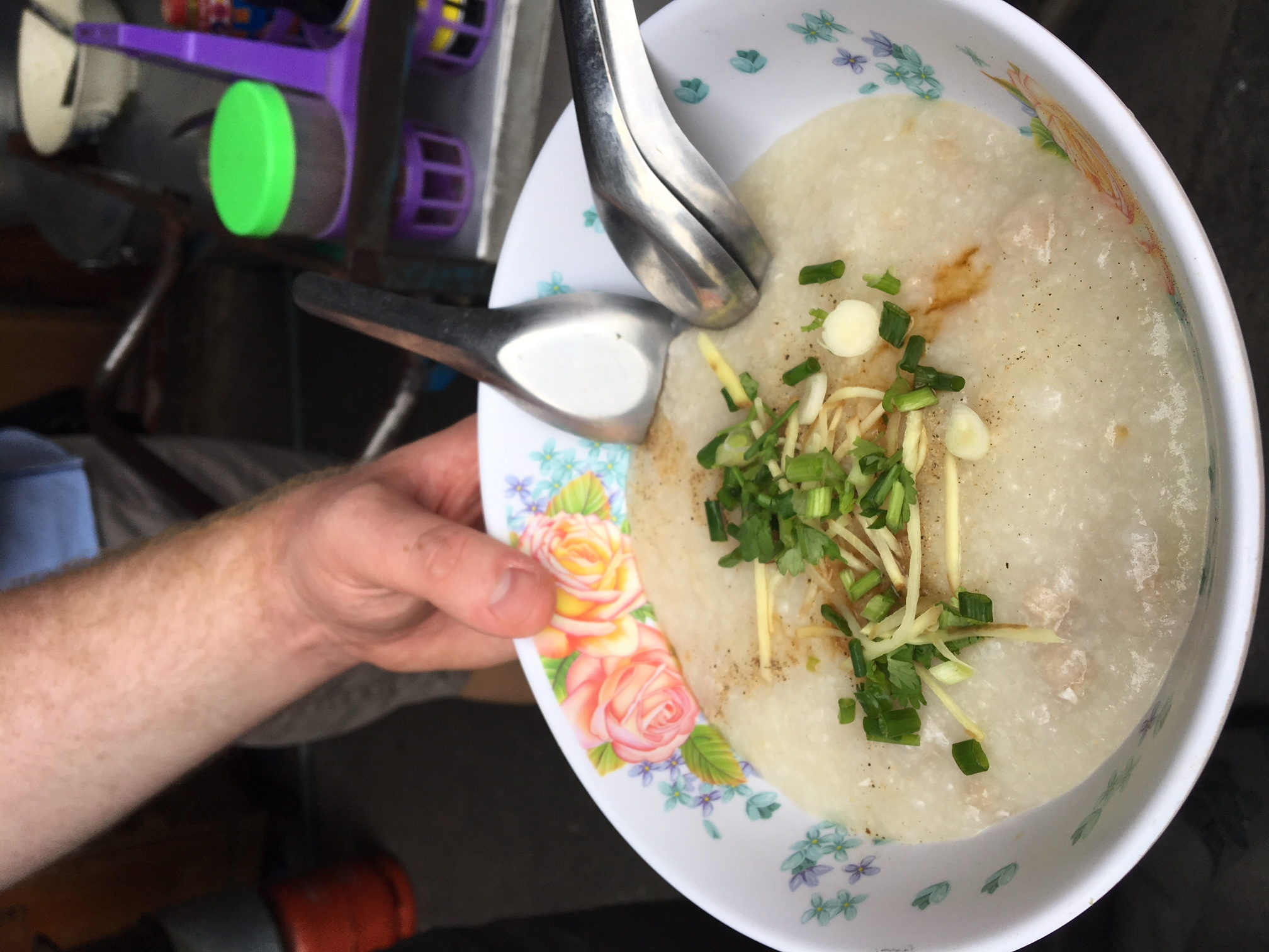 Bowl with rice porridge, ginger, spring onion topping