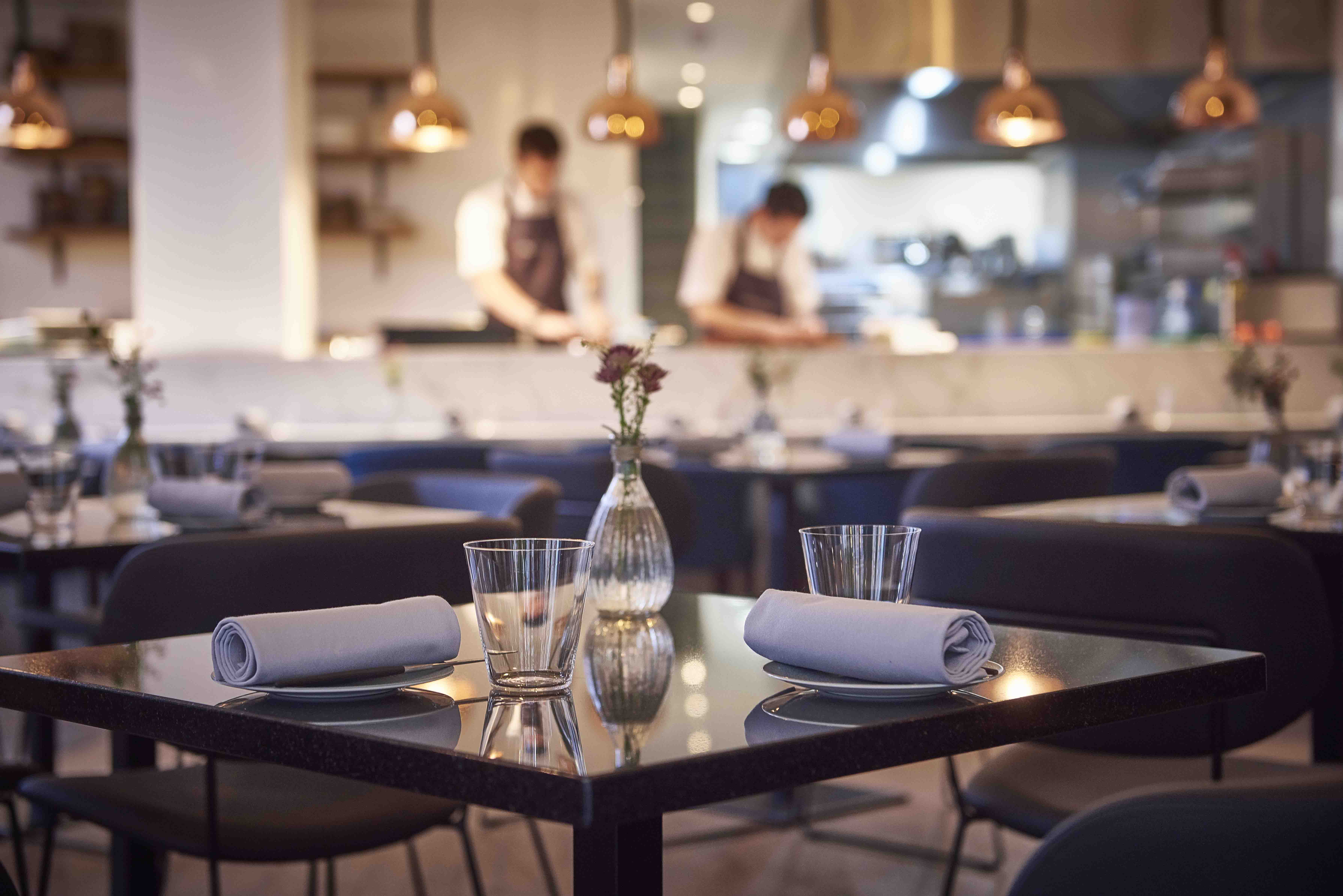 Table set at Frog by Adam Handling with open kitchen in background