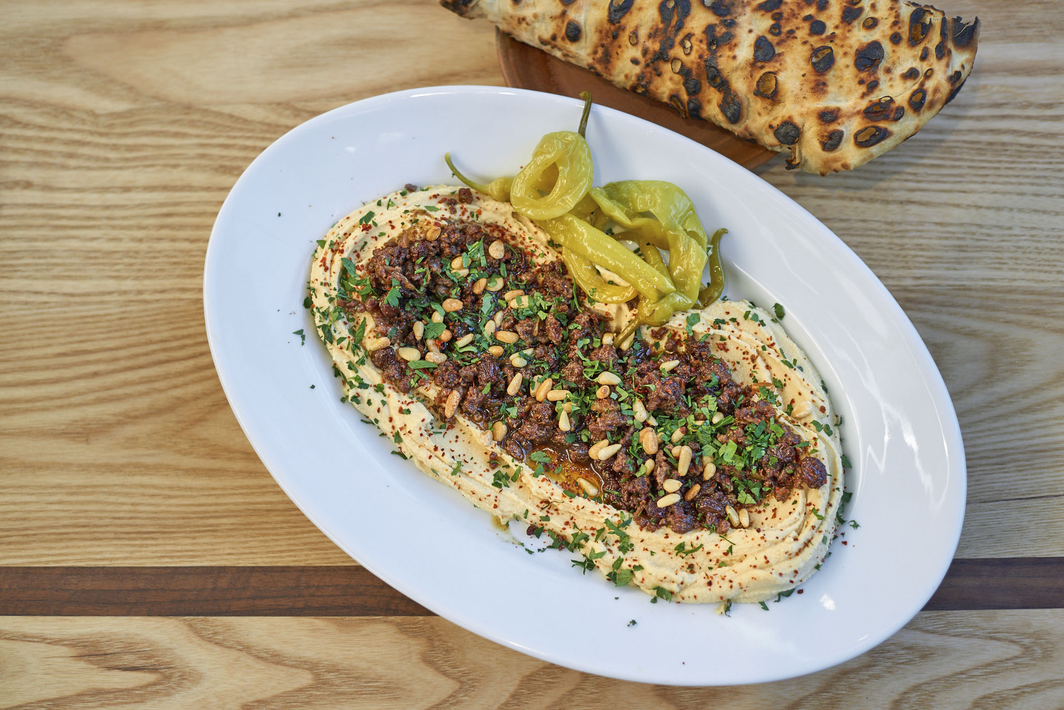 Baharat-spiced lamb, hummus, pine nuts, raisins and flatbreads