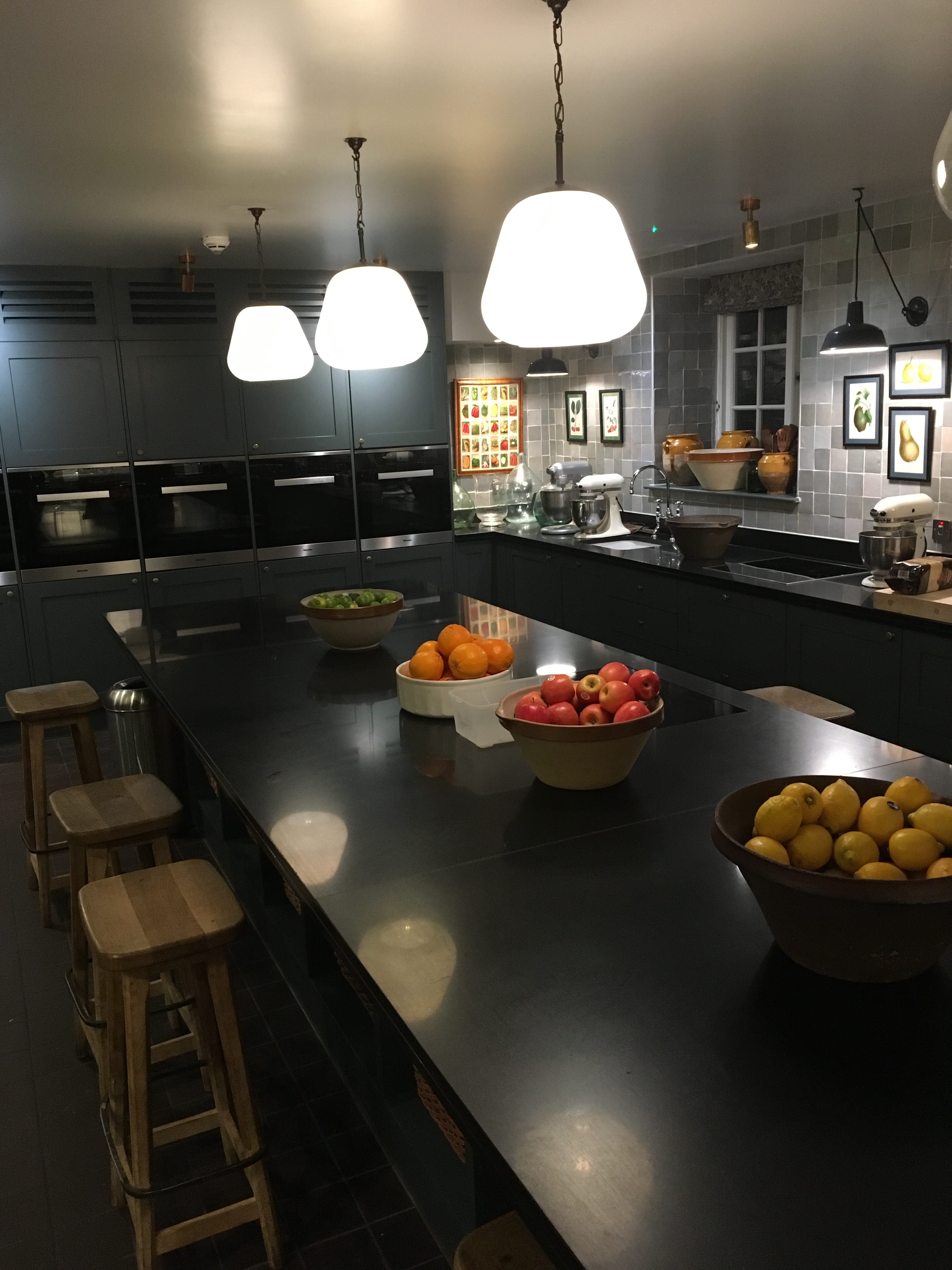 A room with a large worktop with stools and bowls of fruits, with ovens behind