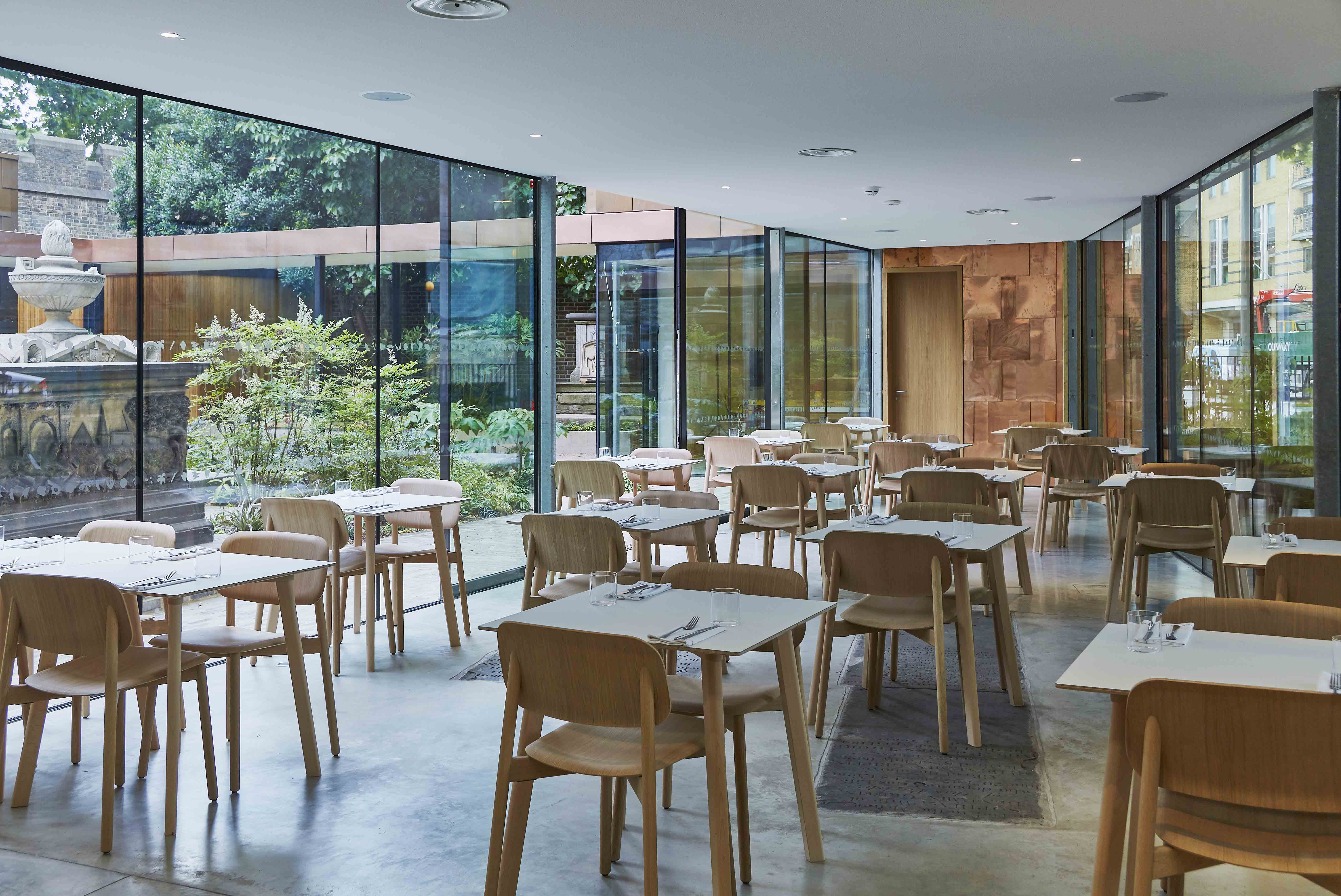 Wooden chairs and tables in a room with glass walls