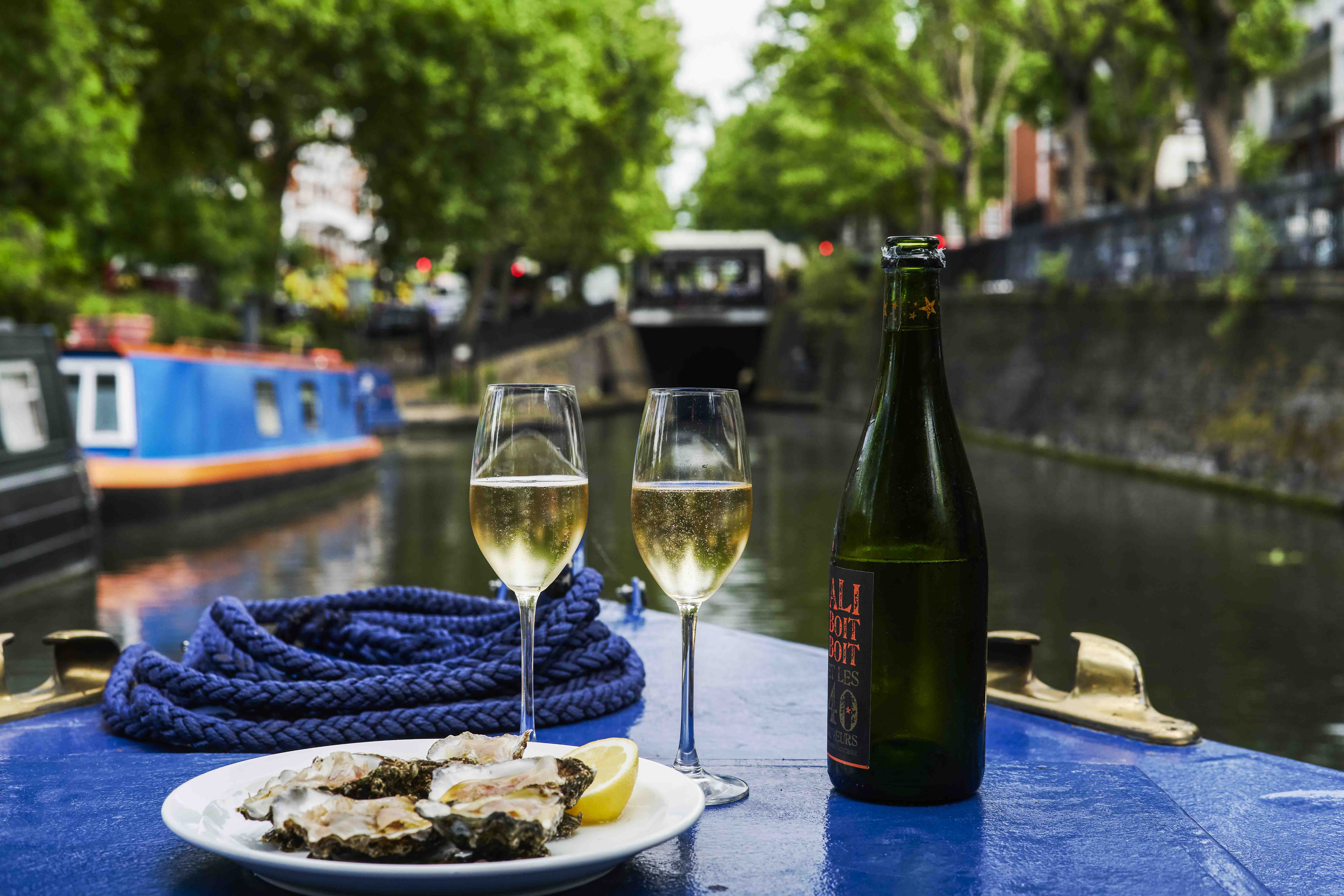 Two glasses of sparkling wine and a plate of oysters on the front of a barge on the canal