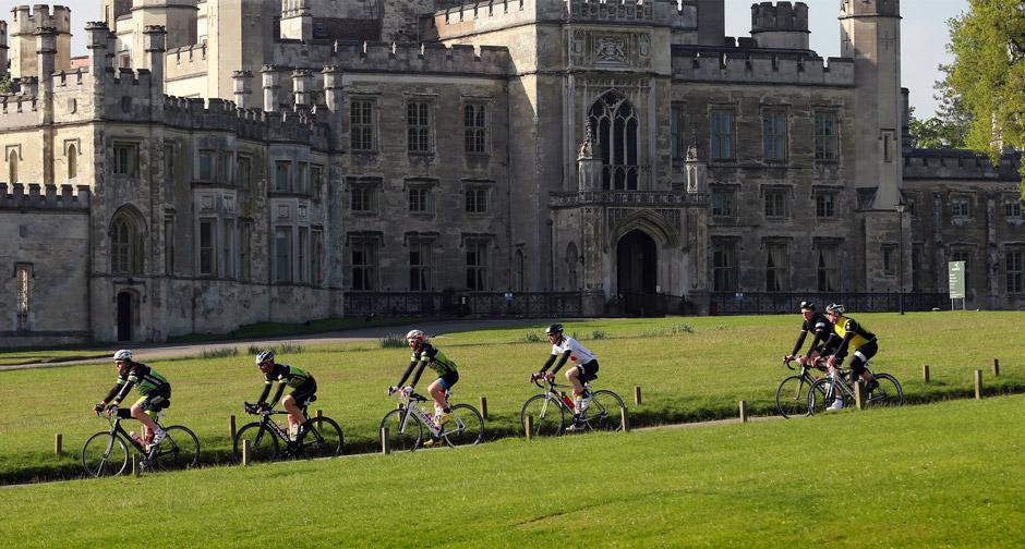 Cyclists riding past a castle
