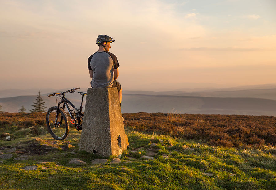 A man sat on a stane next to his mountain bike