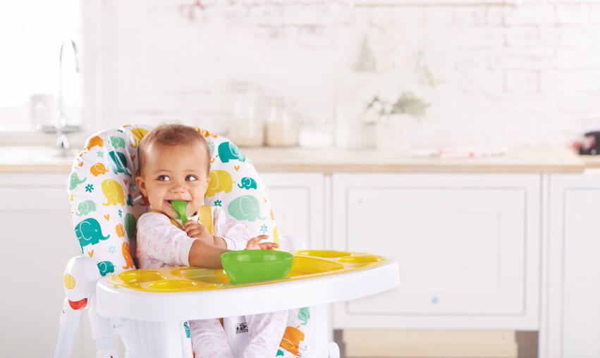 Baby eating food in a highchair