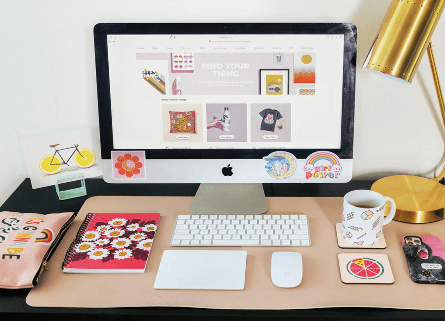 Desk with a iMac and various items of stationery