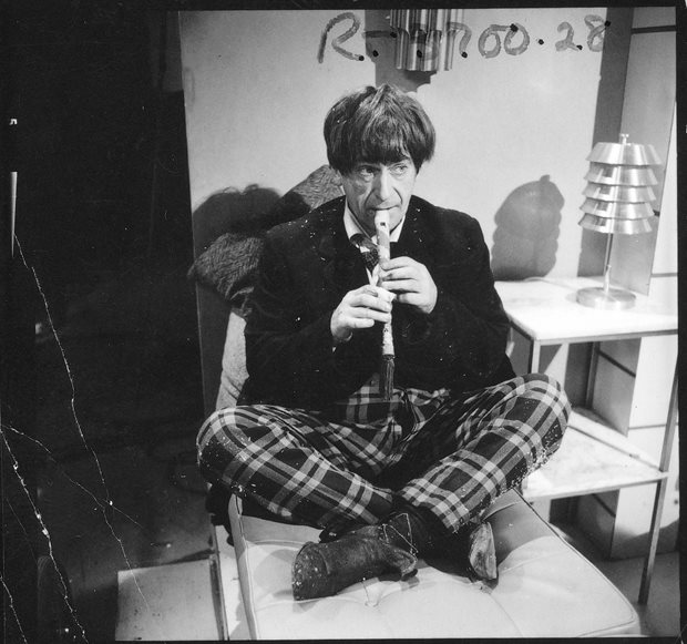 Patrick Troughton playing his recorder in the rest room set of the Vulcan colony. Here you can see the plaster on his index finger, and that his trousers are also speckled in sawdust or polystyrene. Shot number RT 3700 28.