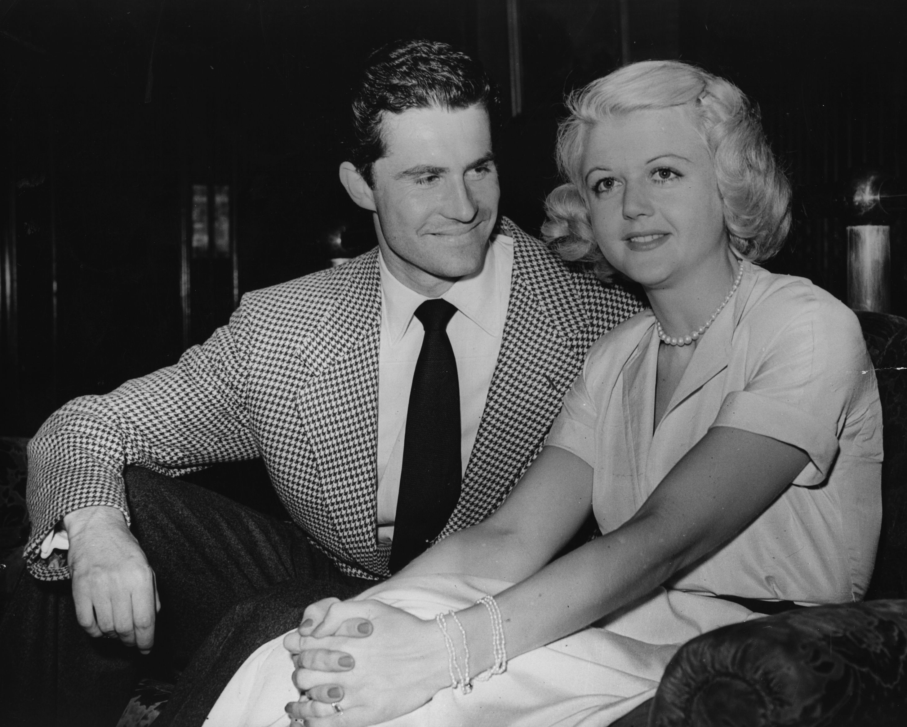 27th July 1949: British actress Angela Lansbury with Peter Shaw on their arrival at London Airport before their wedding. (Photo by Keystone/Getty Images) TL