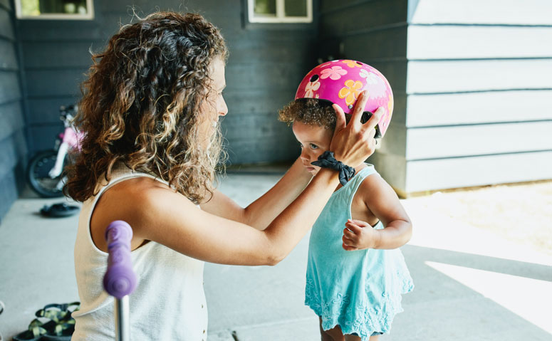Mother placing a bike helmet on daughters head