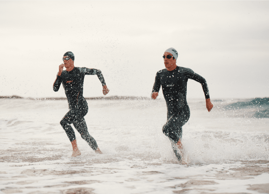 Two triathlon swimmers running to the shore