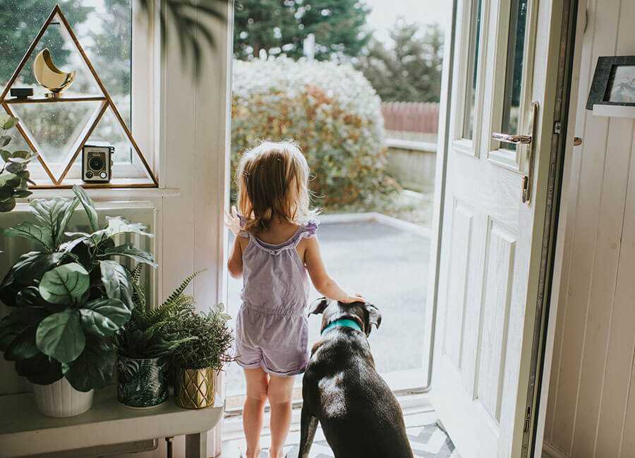 Girl and dog looking out from the front door