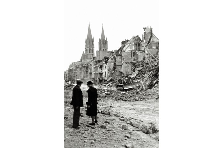 An older couple is watching a Canadian soldier with a bulldozer working in the ruins of a house in the rue de Bayeux.10th July 1944. The church towers in the background have survived the Allied bombing intact. Caen, Normandy, France. (Photo by Galerie Bilderwelt/Getty Images)