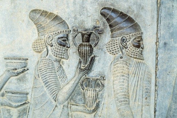A stone relief depicting men bringing gifts to the king, c500 BC. (Getty Images)