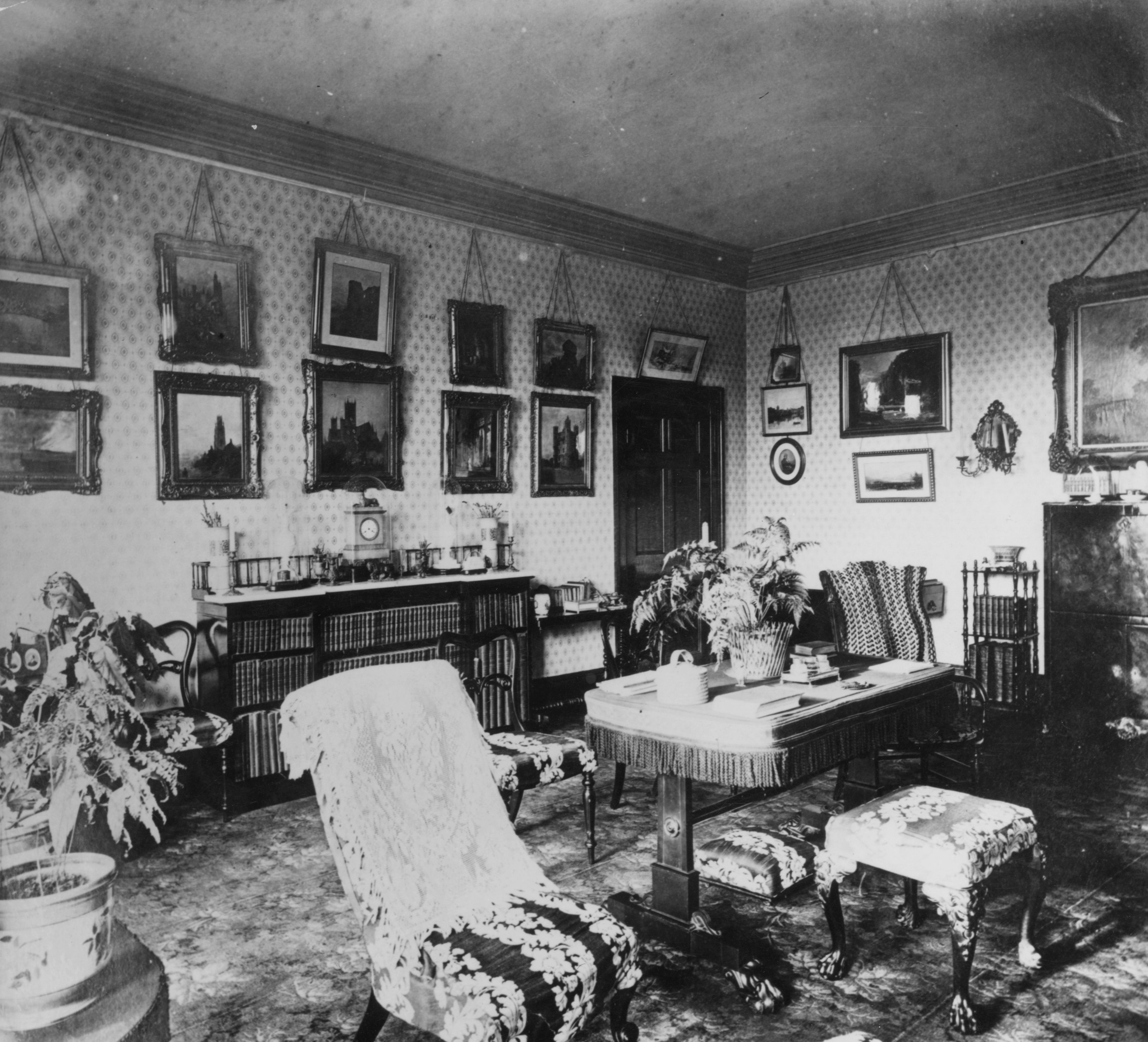 A Victorian drawing room with pictures in heavy frames and ornately covered furniture, c1860. (Hulton Archive/Getty Images)