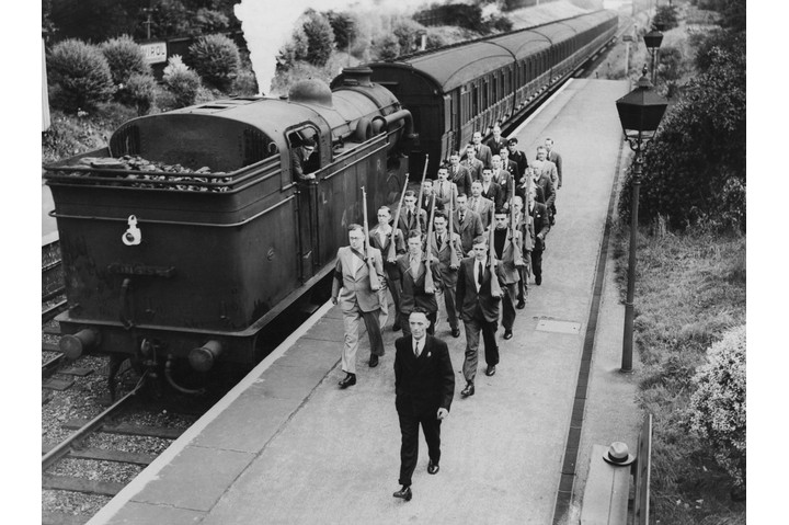 Members of the Palmers Green and Winchmore Hill LNER (London and North Eastern Railway) LDV (Local Defence Volunteers) dressed in their civilian clothes march along a platform passing a steam locomotive on 1 July 1940 in London. (Photo by Harry Todd/Fox Photos/Hulton Archive/Getty Images)