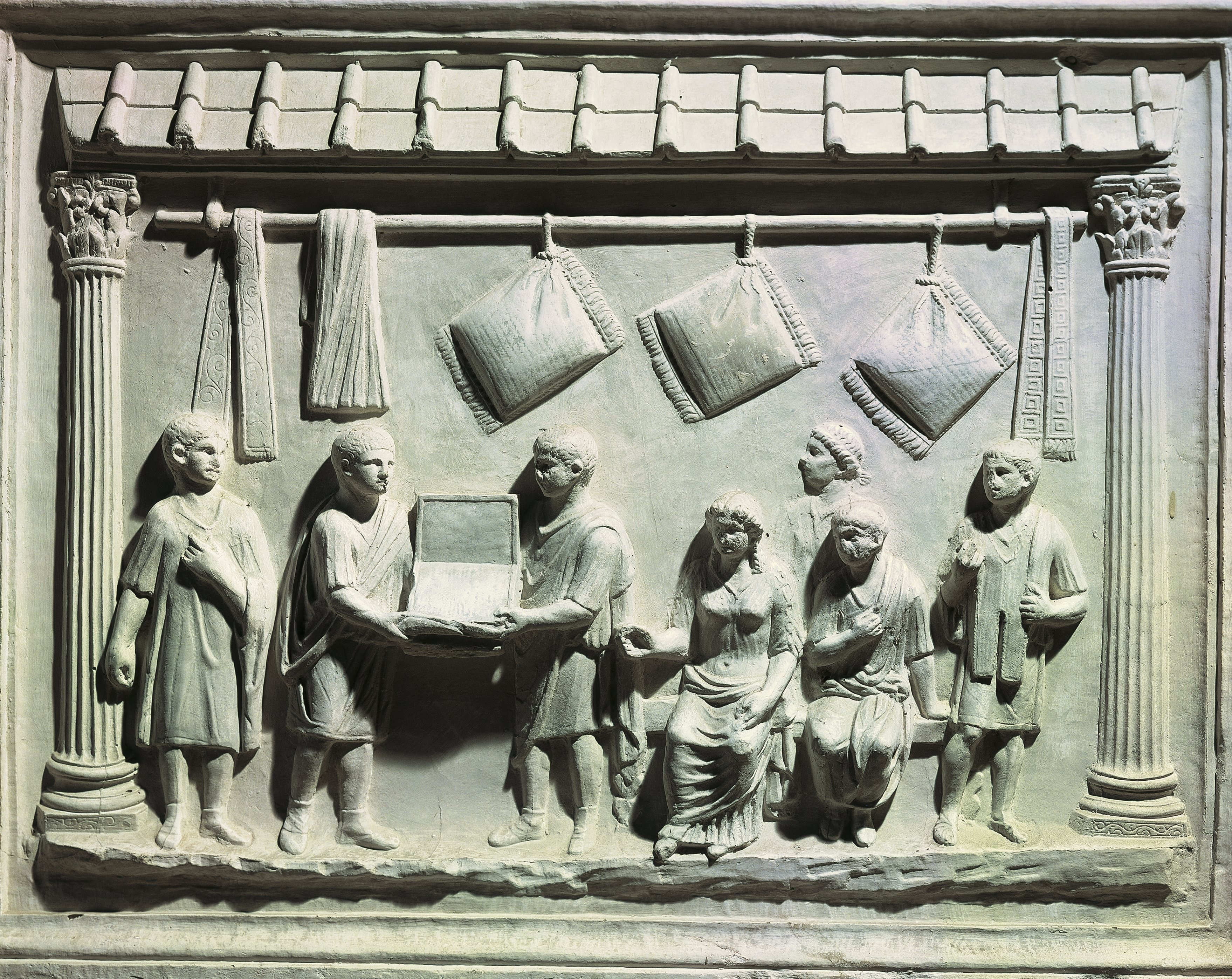 Relief depicting interior of belt and cushion shop, with owner and clerks showing goods to seated buyers and slaves