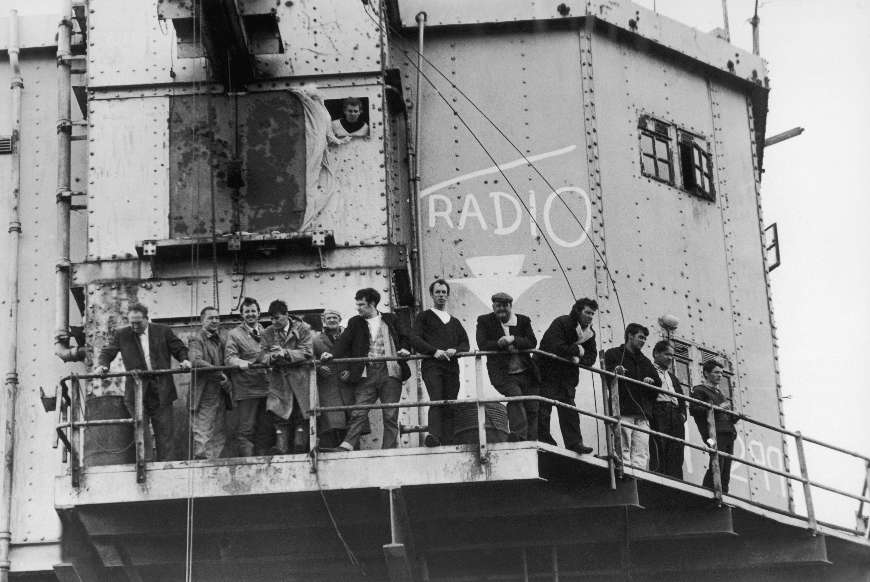 Men line the rails around Radio City, on an abandoned naval fort in the Thames Estuary. In June 1966, Radio City was at the centre of a murder enquiry that would lead to the closure of Britain's pirate radio stations. (Photo by Keystone-France/Gamma-Keystone via Getty Images)