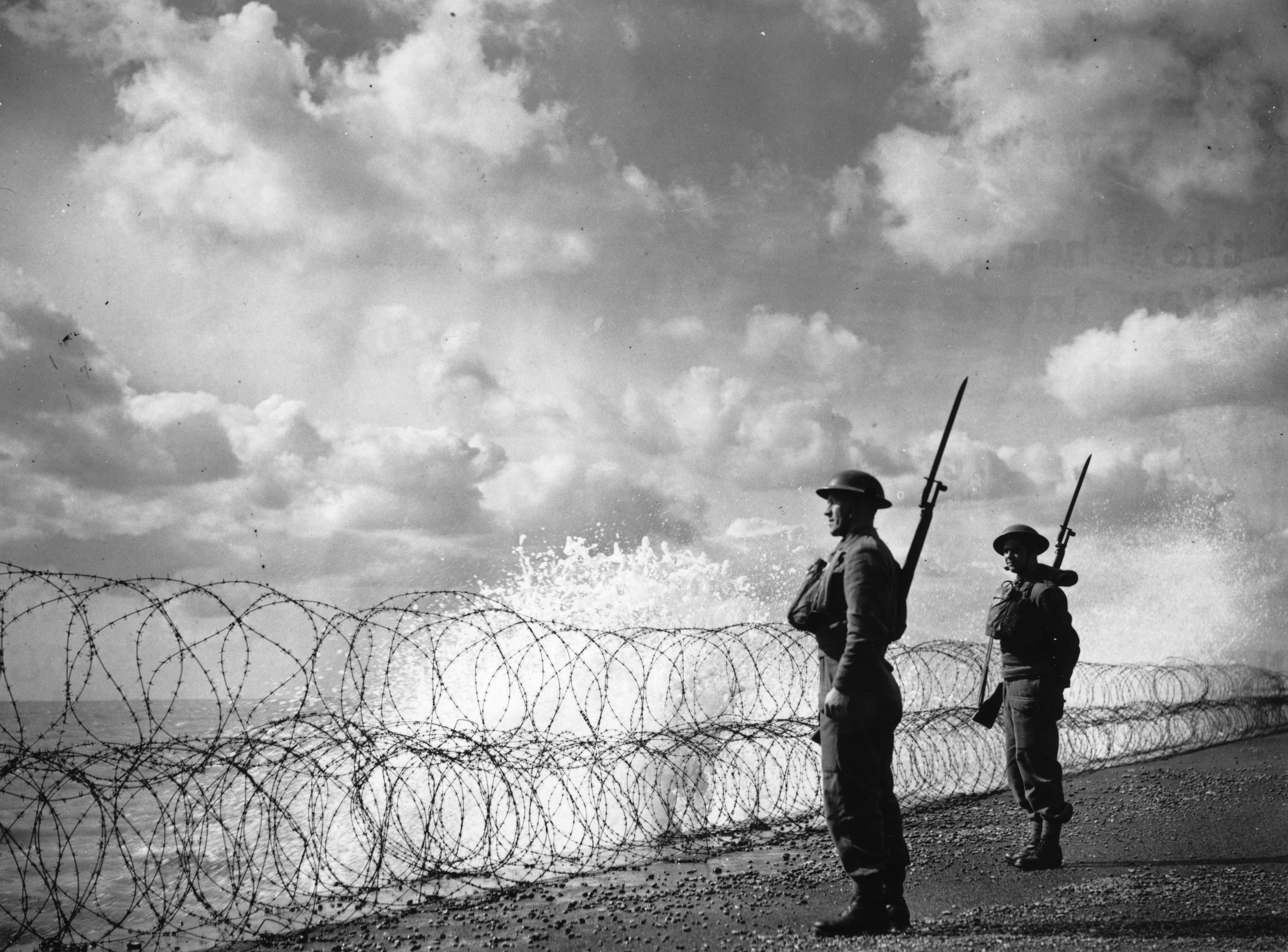 Soldiers guard England's south coast behind a bank of banned wire on 2 September 1940