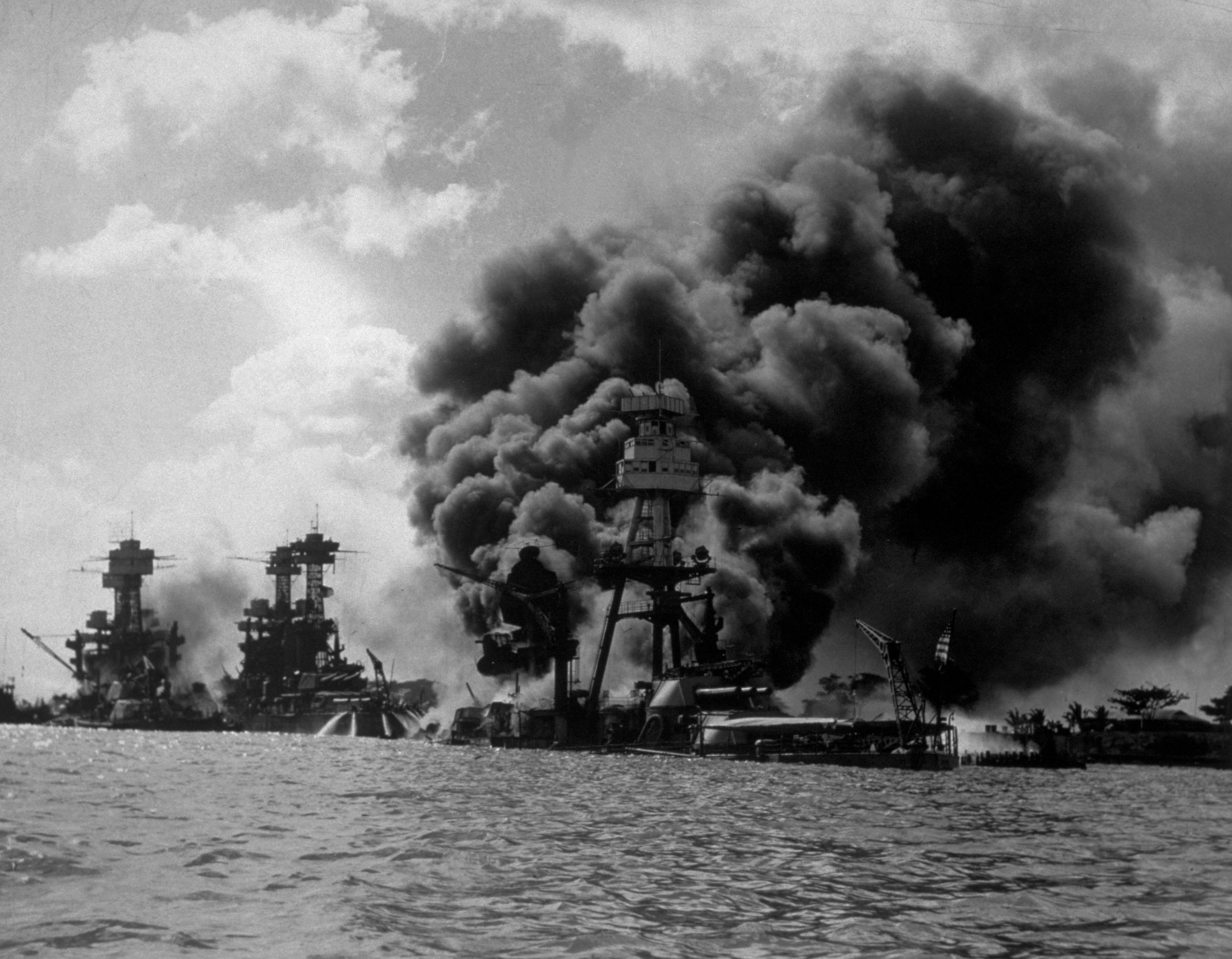 The USS Arizona burning in Pearl Harbor following the Japanese attack. To the left of her are USS Tennessee and the sunken USS West Virginia. (Photo by Hulton Archive/Getty Images)