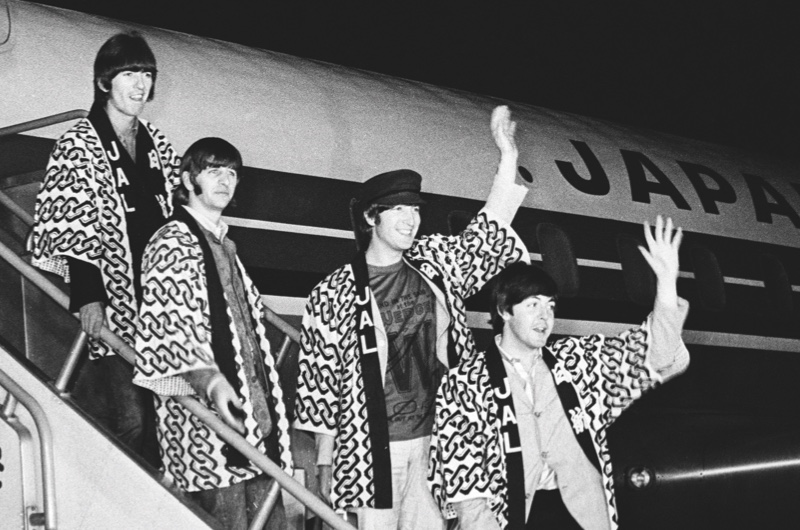 Dressed in happi coats often worn by Japanese workmen the Beatles arrive in Tokyo , Japan . 29th June 1966